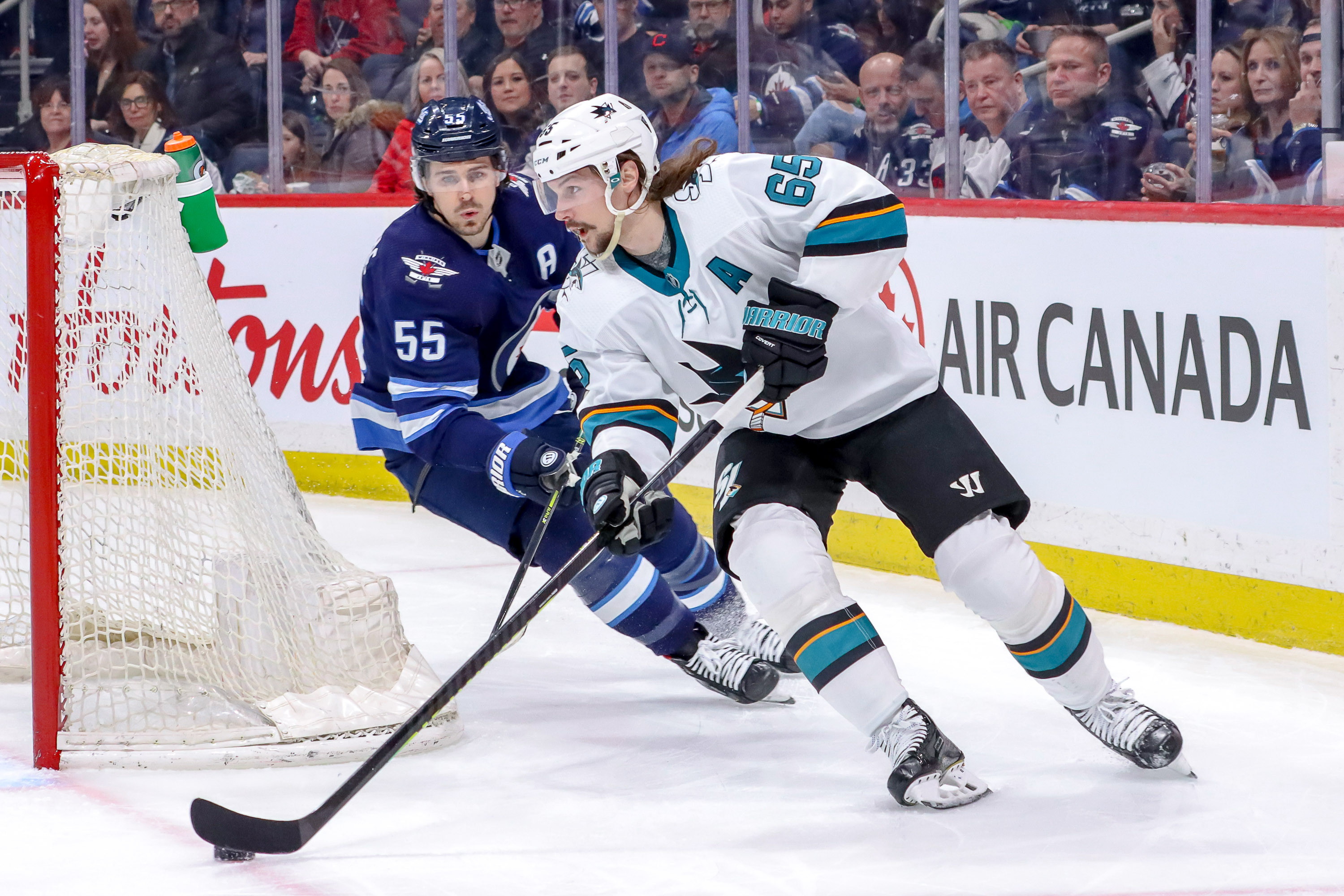 Erik Karlsson #65 of the San Jose Sharks plays the puck around the net as Mark Scheifele #55 of the Winnipeg Jets gives chase during first period action at the Bell MTS Place on February 14, 2020 in Winnipeg, Manitoba, Canada.