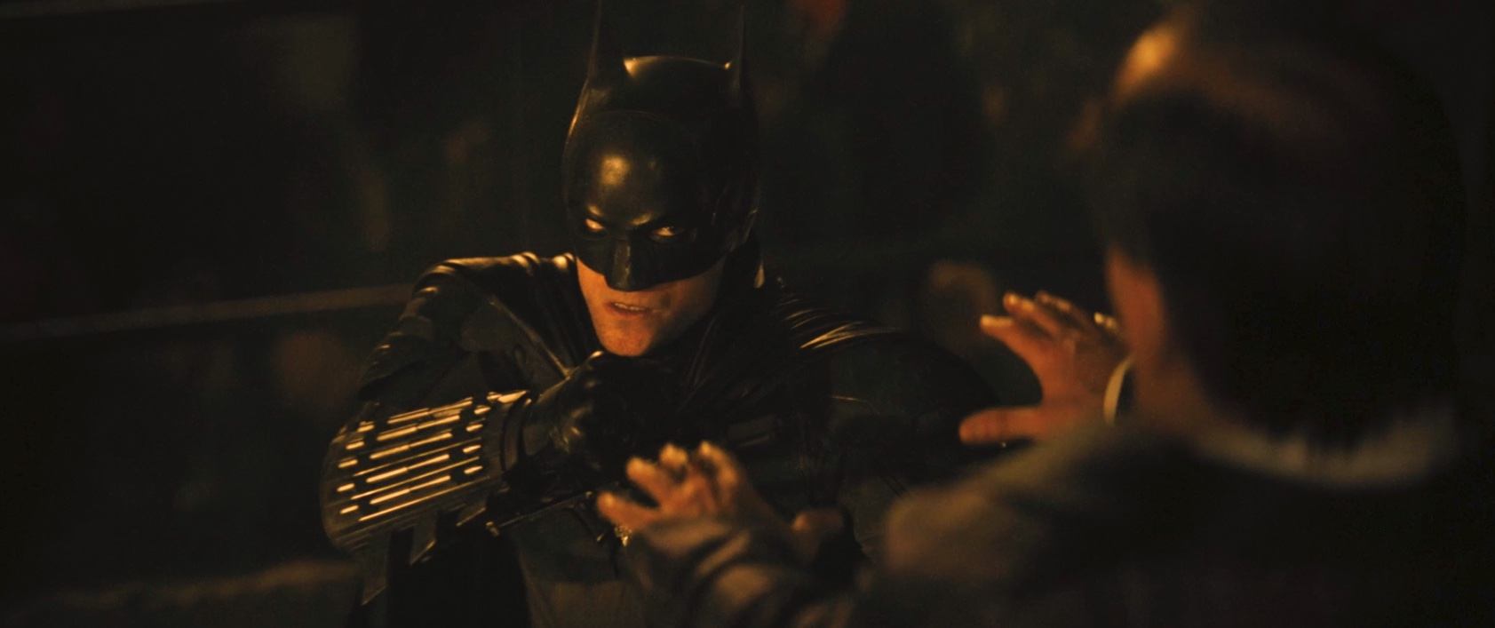 Robert Pattinson's Batman fights the Penguin in the glow of a fire