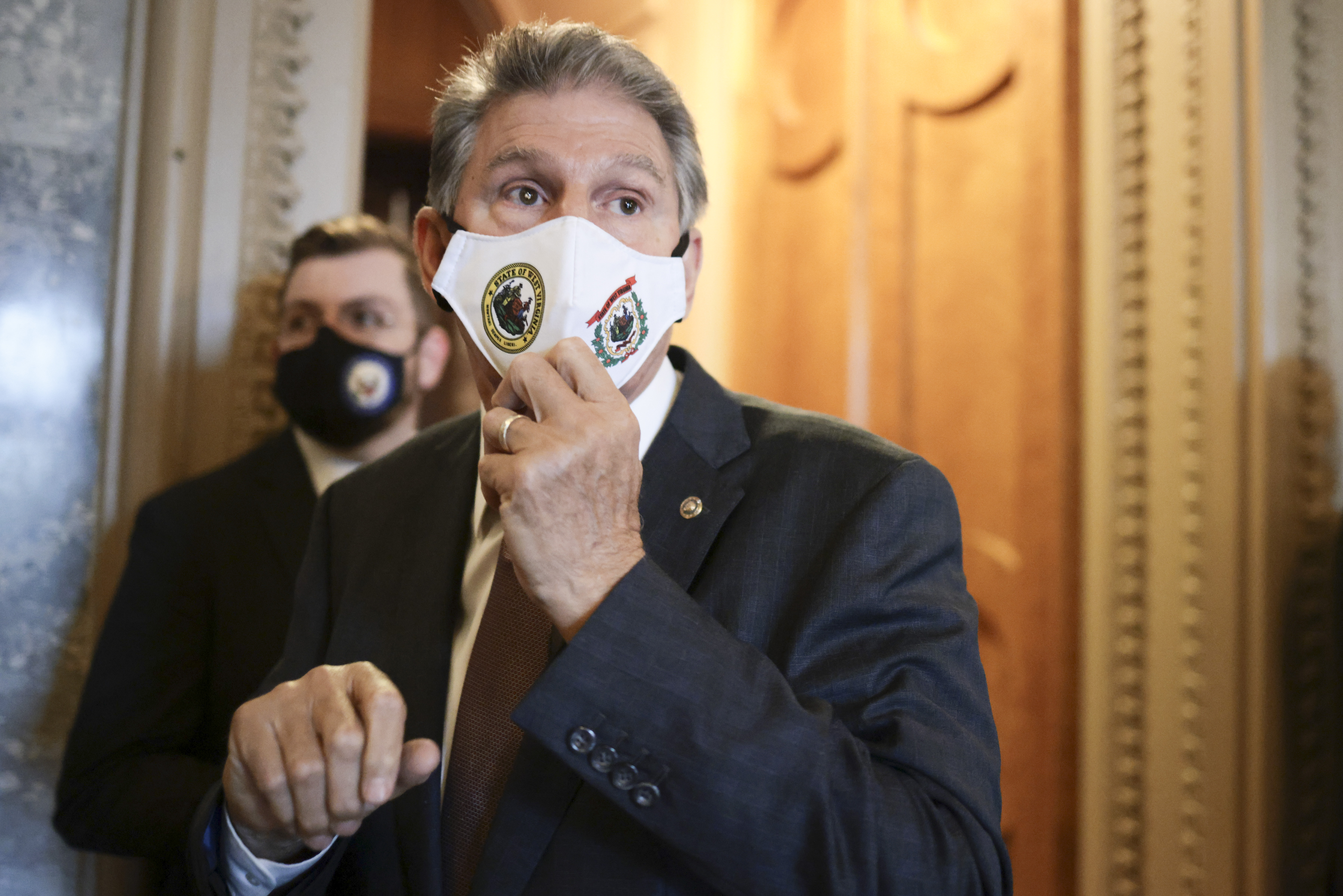 Sen. Joe Manchin (D-WV) adjusts his mask as he speaks to reporters on Capitol Hill.