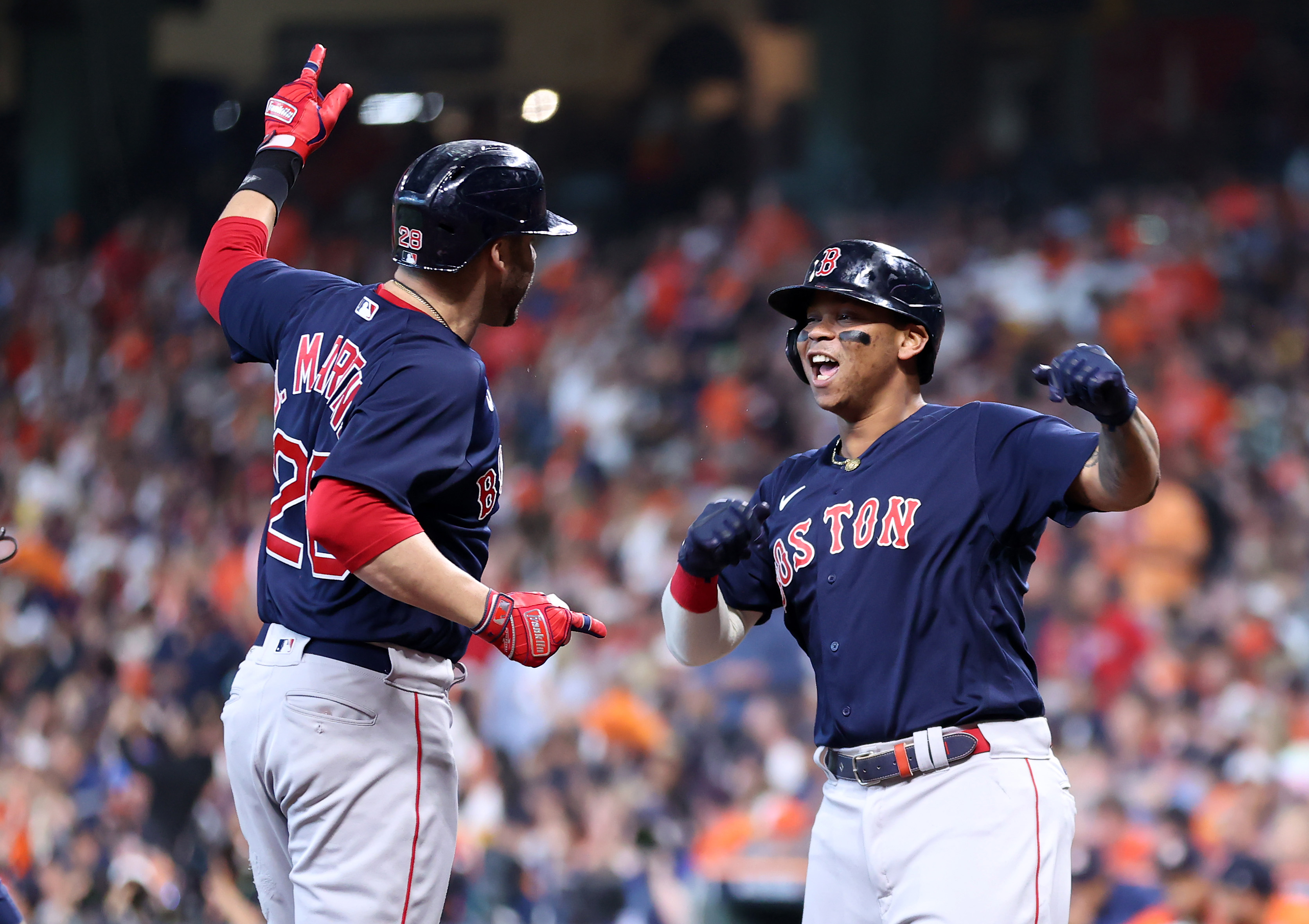 J.D. Martinez of the Boston Red Sox is congratulated by Rafael Devers after he hit a grand slam home run against the Houston Astros in the first inning of Game Two of the American League Championship Series at Minute Maid Park on October 16, 2021 in Houston, Texas.
