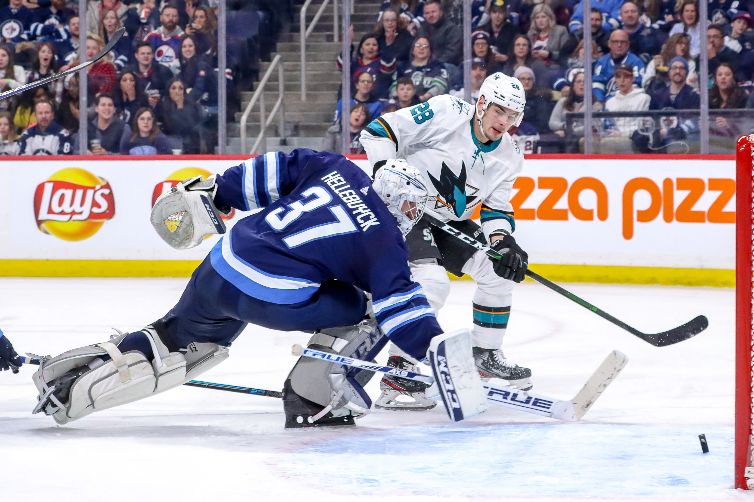 Timo Meier #28 of the San Jose Sharks shoots the puck past goaltender Connor Hellebuyck #37 of the Winnipeg Jets for a third period goal at the Bell MTS Place on February 14, 2020 in Winnipeg, Manitoba, Canada.