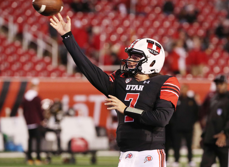 Utah Utes quarterback Cameron Rising, wearing a white helmet and black jersey, warms up