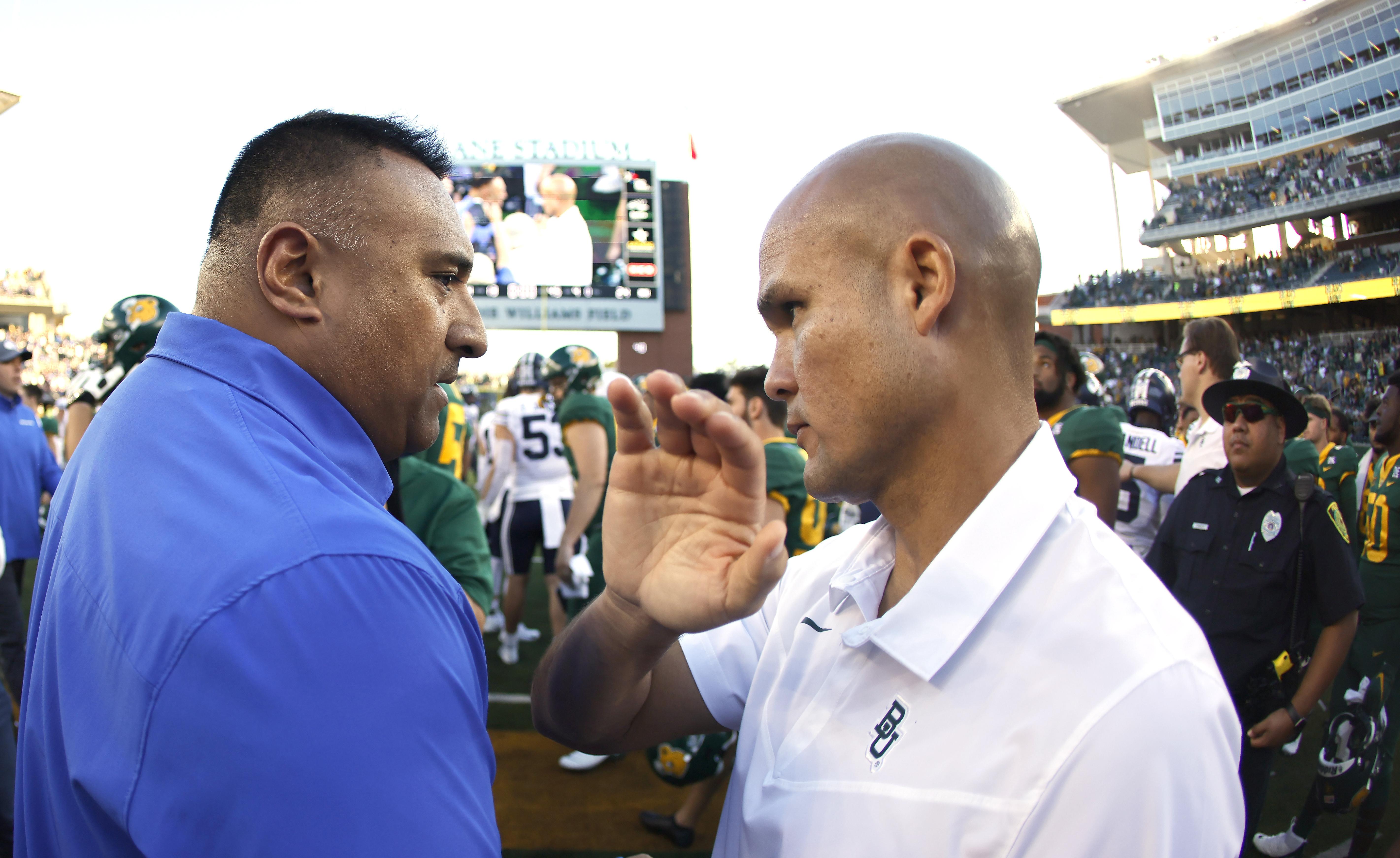BYU head coach Kalani Sitake, left, meets Baylor head coach Dave Aranda on the field.