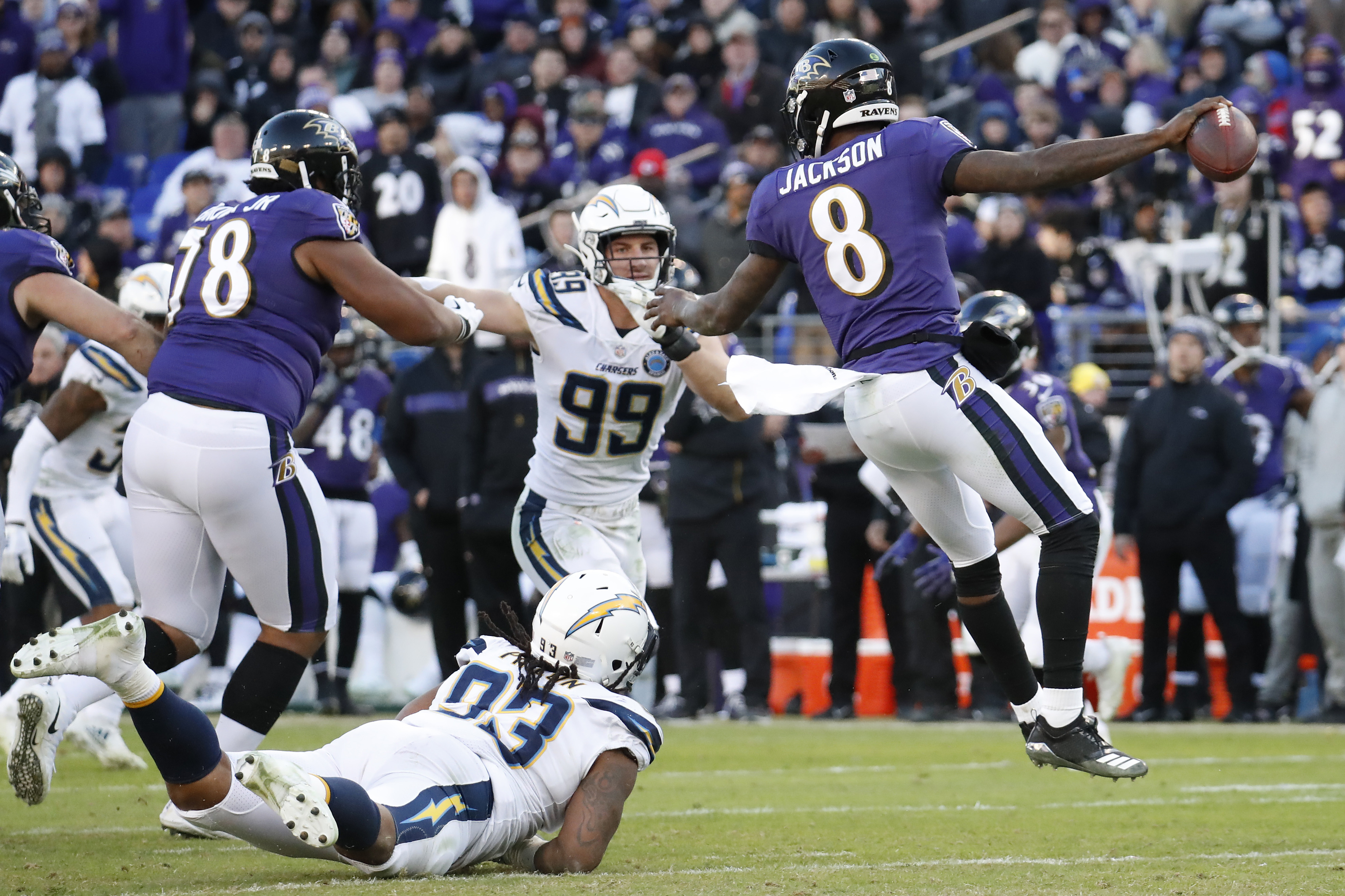 Baltimore Ravens quarterback Lamar Jackson (8) scrambles from Los Angeles Chargers defensive tackle Darius Philon (93) and Chargers defensive end Joey Bosa (99) in the fourth quarter in a AFC Wild Card playoff football game at M&T Bank Stadium. The Chargers won 23-17.
