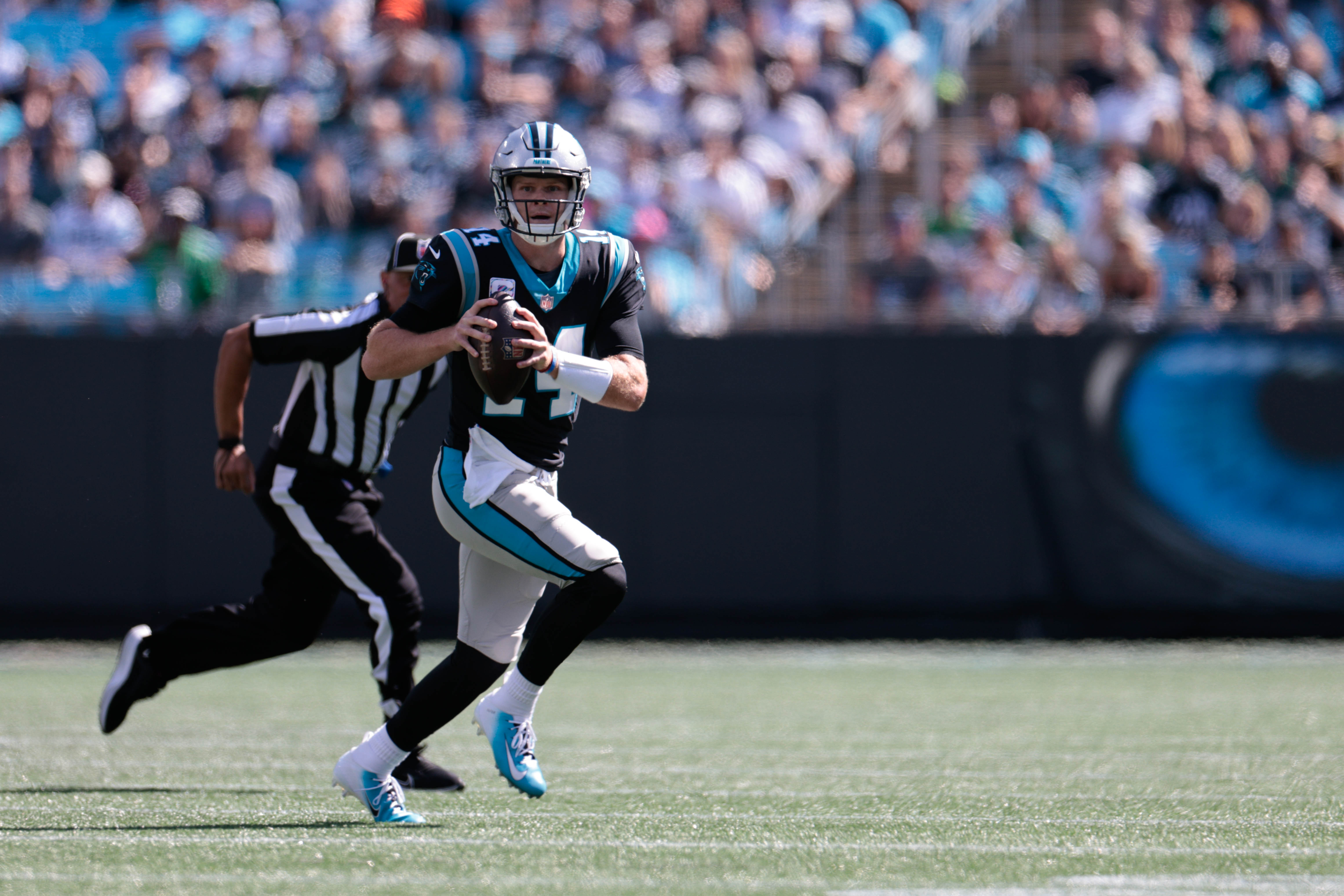 Carolina Panthers quarterback Sam Darnold (14) scrambles with the ball during the first half against the Philadelphia Eagles at Bank of America Stadium.