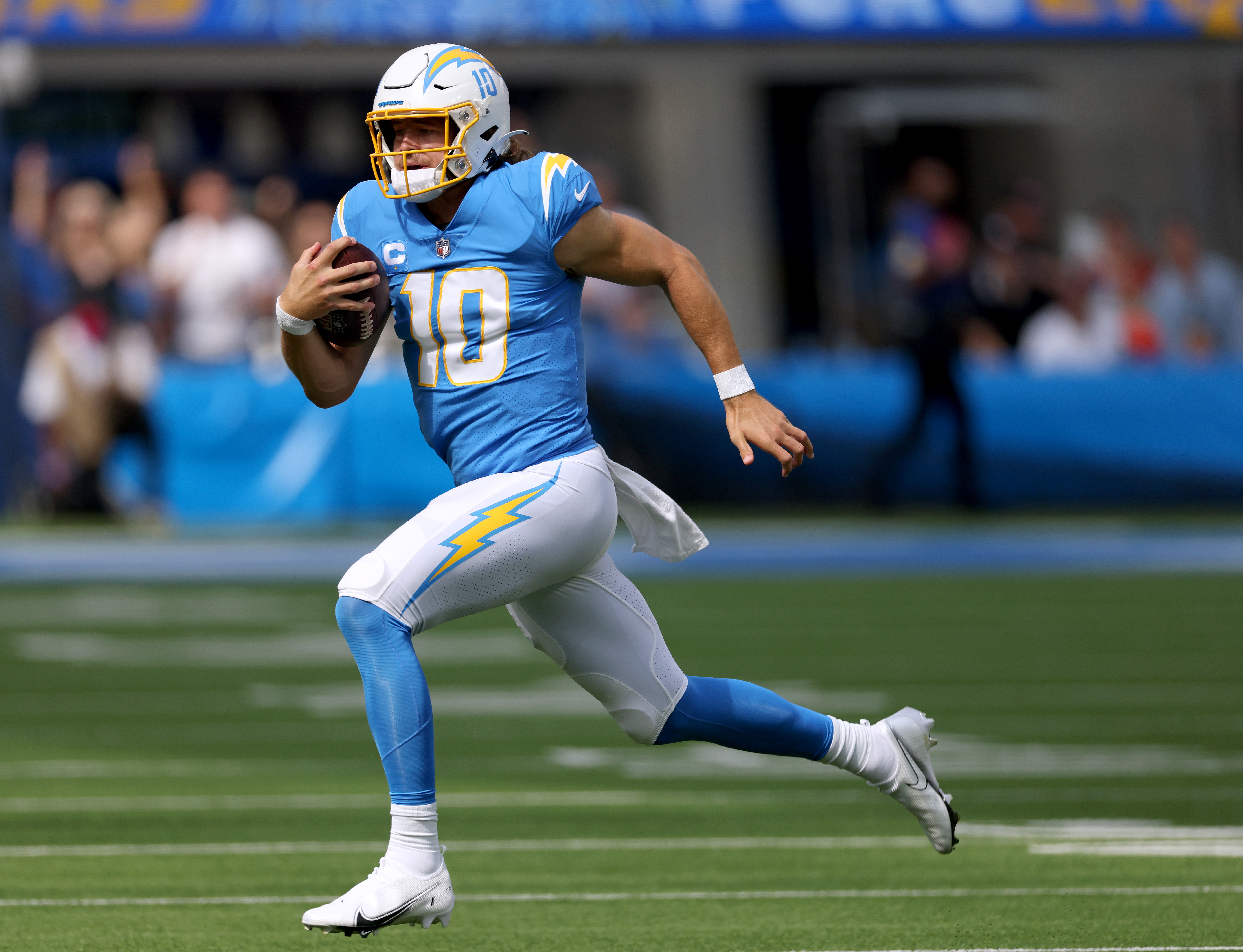 Justin Herbert #10 of the Los Angeles Chargers runs with the ball during a 47-42 win over the Cleveland Browns at SoFi Stadium on October 10, 2021 in Inglewood, California.
