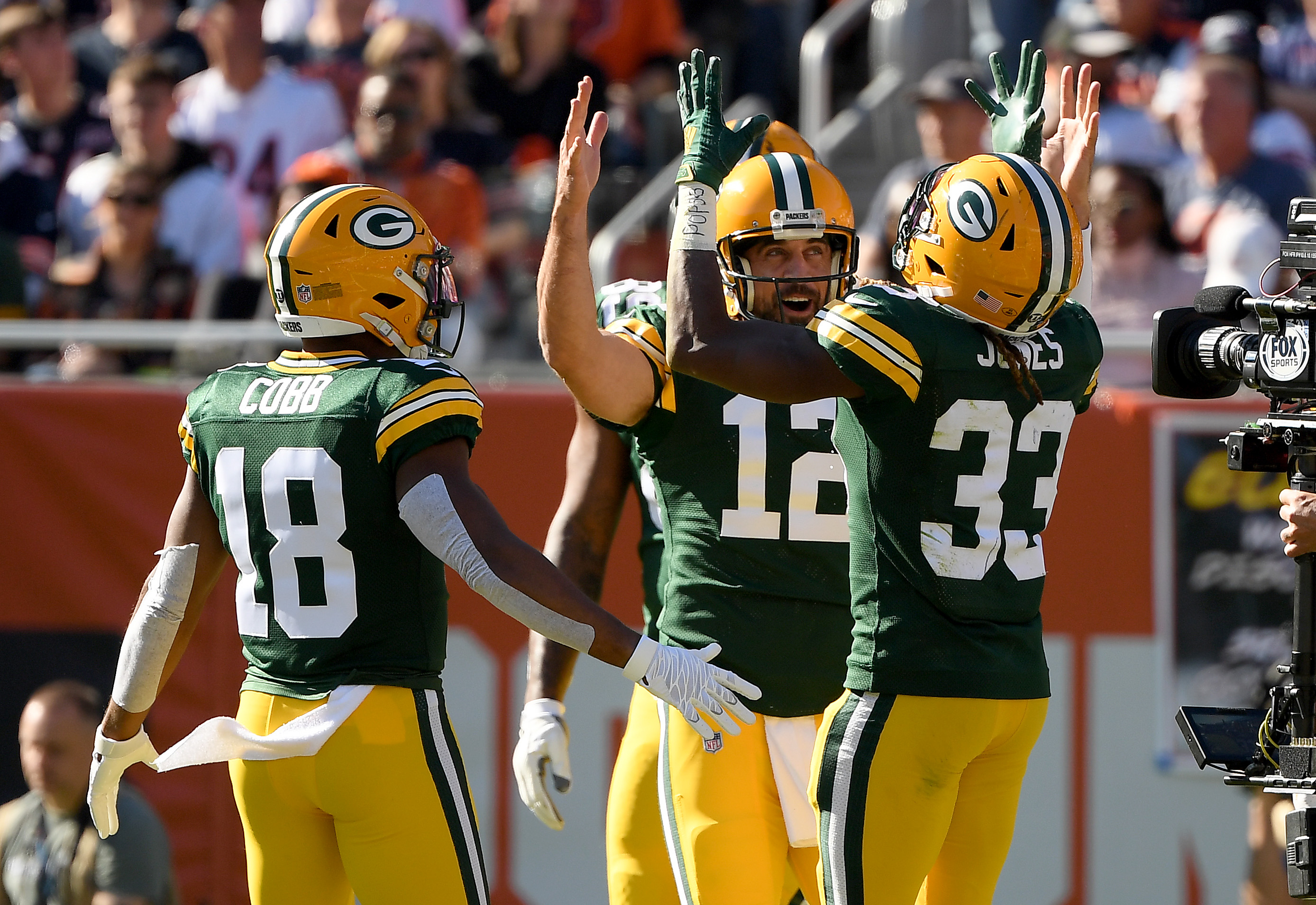 Aaron Rodgers (12) celebrates with Randall Cobb (18) and Aaron Jones (33) after scoring a touchdown in the fourth quarter against the Bears.