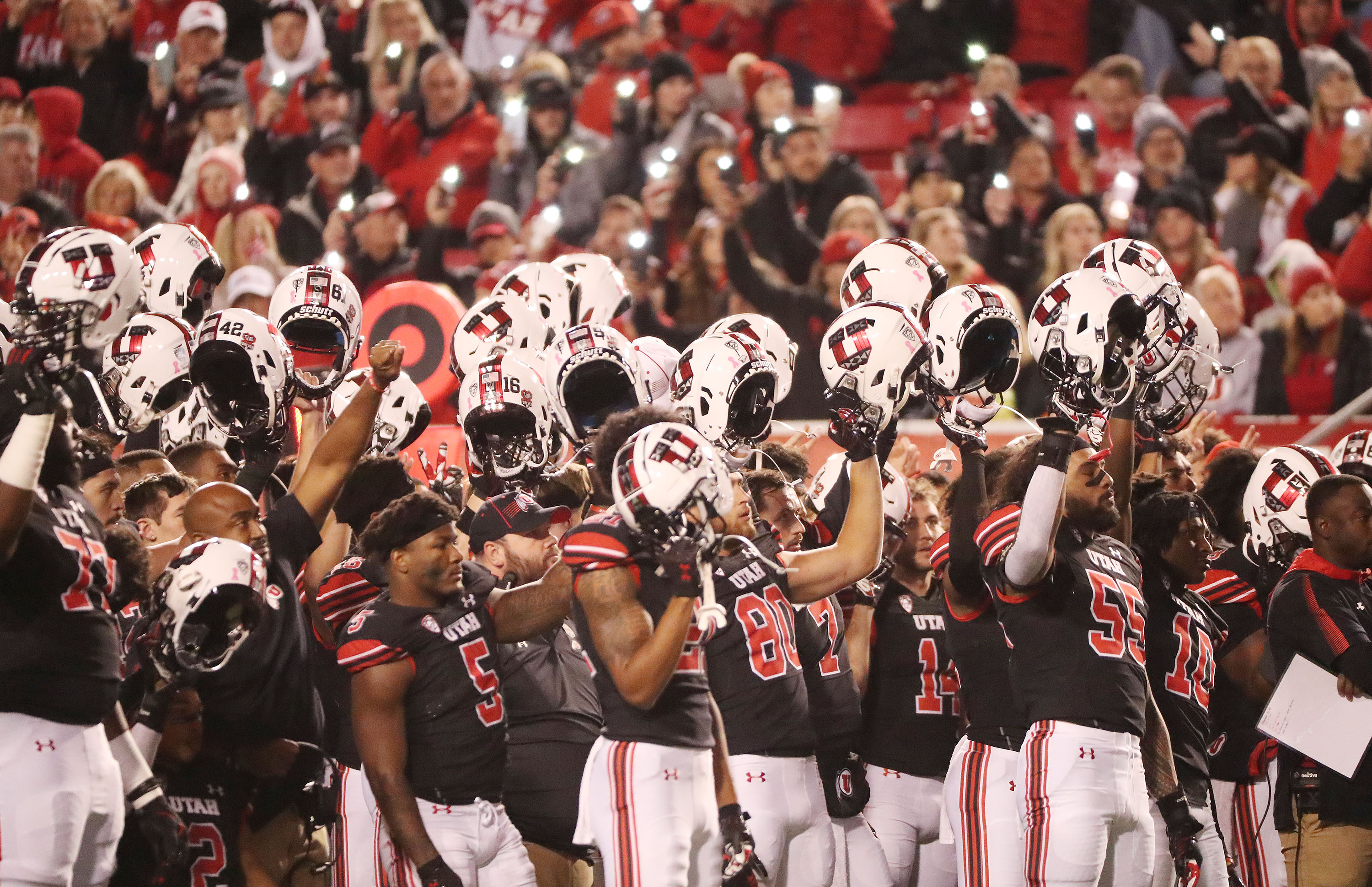 Utah players hold their helmets up