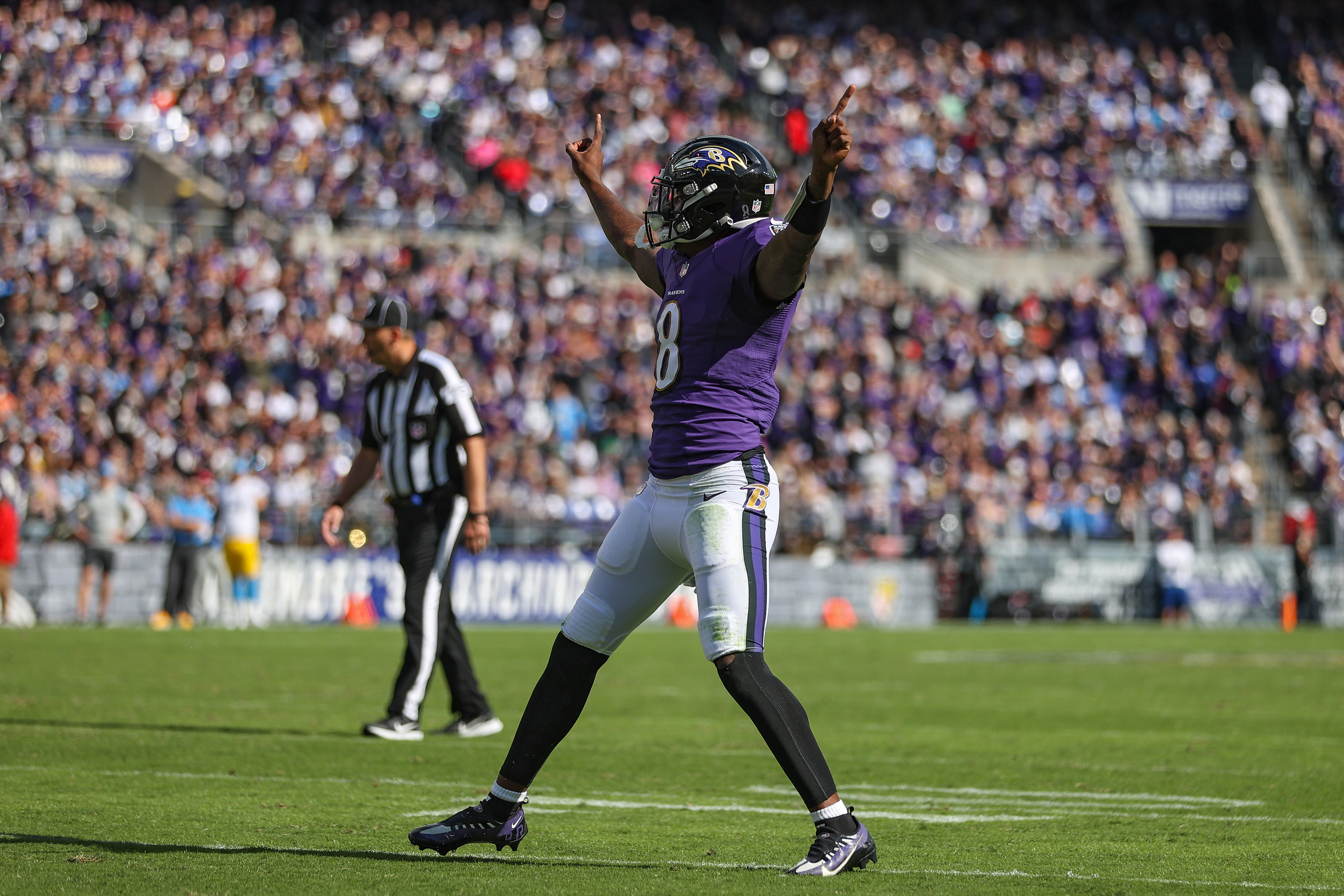 Quarterback Lamar Jackson #8 of the Baltimore Ravens celebrates a touchdown scored by Le'Veon Bell #17 (not pictured) during the second quarter against the Los Angeles Chargers at M&T Bank Stadium on October 17, 2021 in Baltimore, Maryland.