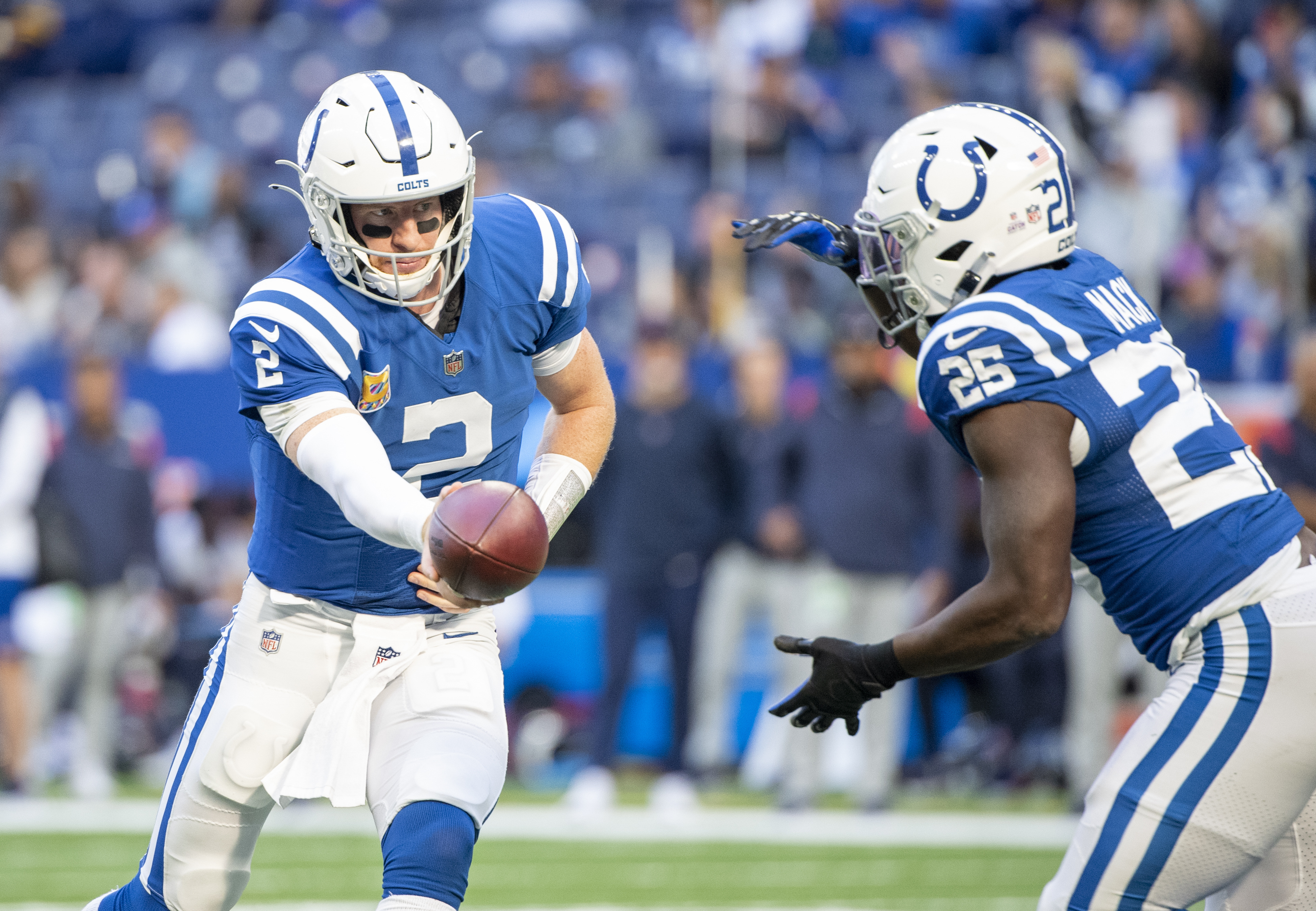 Indianapolis Colts quarterback Carson Wentz (2) hands the ball off to Indianapolis Colts running back Marlon Mack (25) during the second half at Lucas Oil Stadium. The Colts win 31-3.