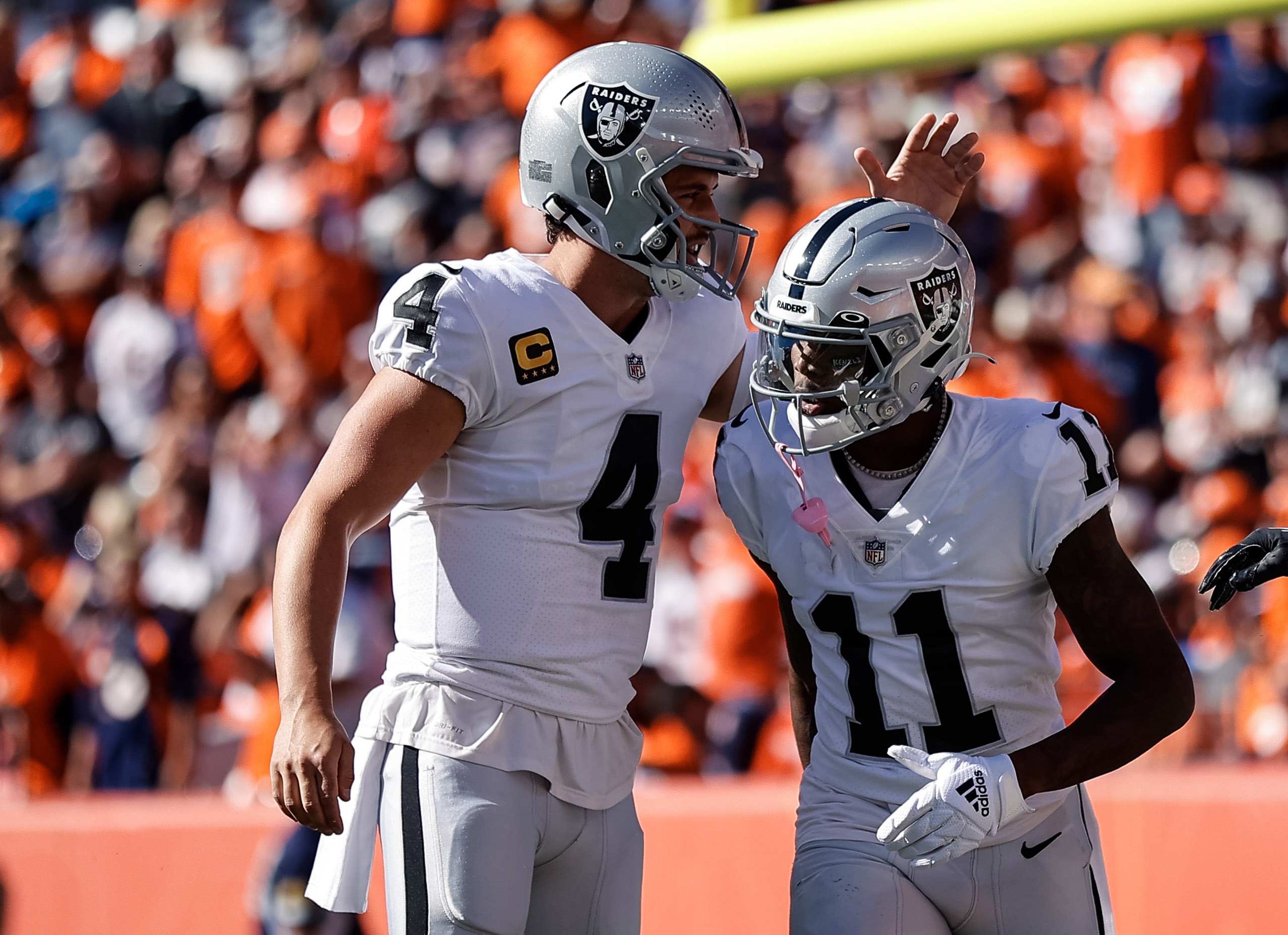 Las Vegas Raiders wide receiver Henry Ruggs III (11) celebrates with quarterback Derek Carr (4) after a touchdown in the first quarter against the Denver Broncos at Empower Field at Mile High.