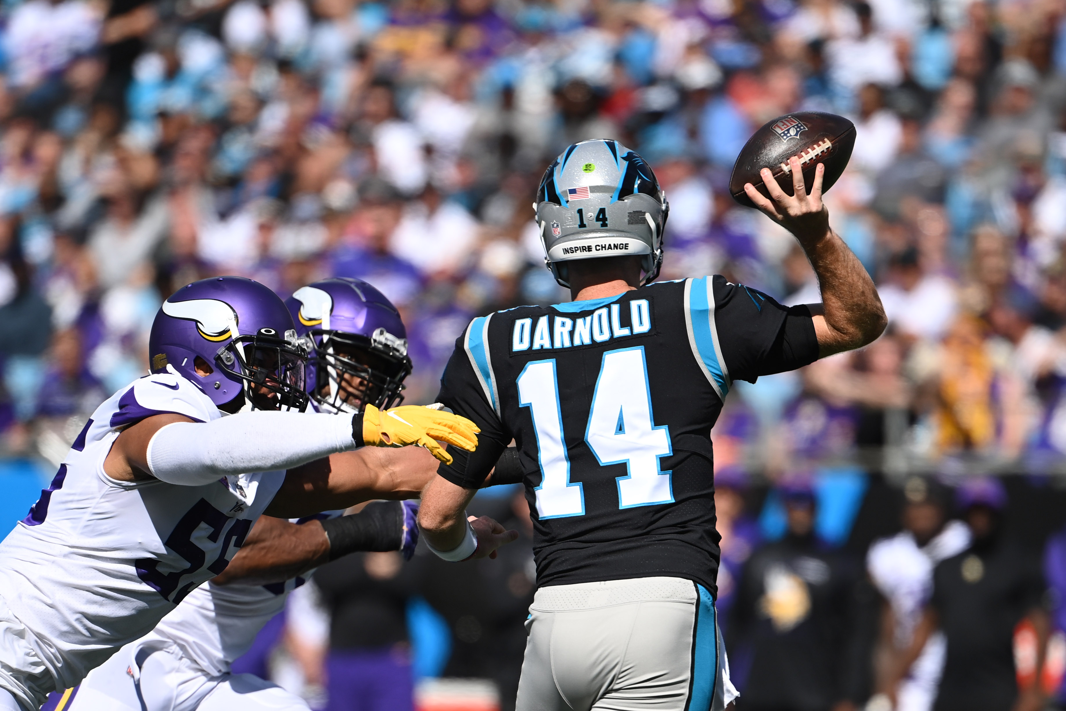 Carolina Panthers quarterback Sam Darnold (14) looks to pass as Minnesota Vikings outside linebacker Anthony Barr (55) and defensive end Danielle Hunter (99) defend in the second quarter at Bank of America Stadium.