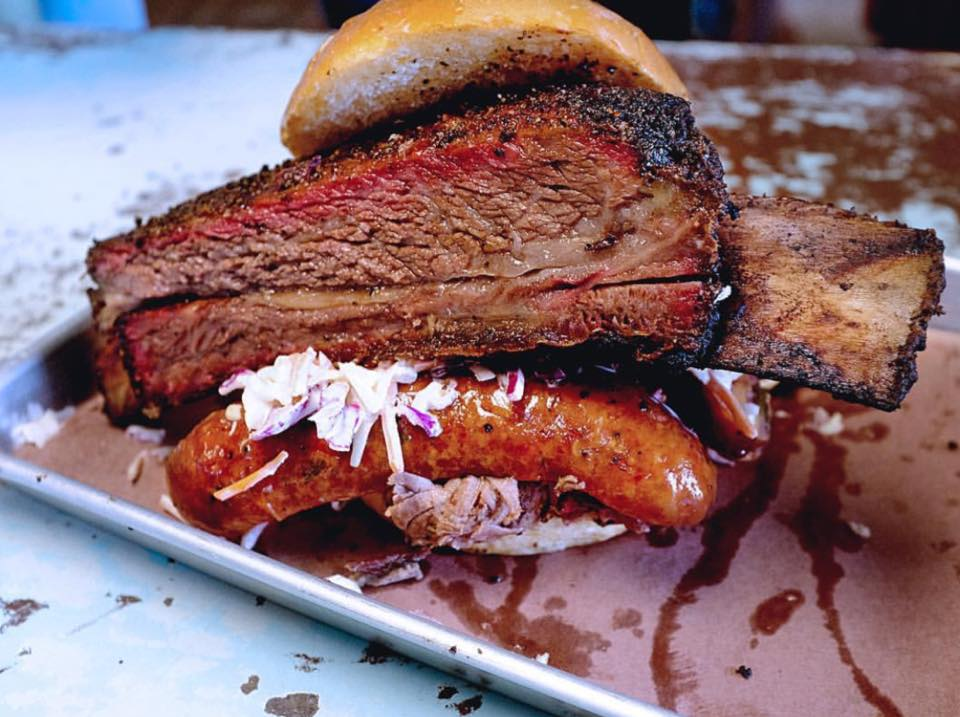 A sandwich of barbecues beef ribs and a sausage link on a toasted bun.