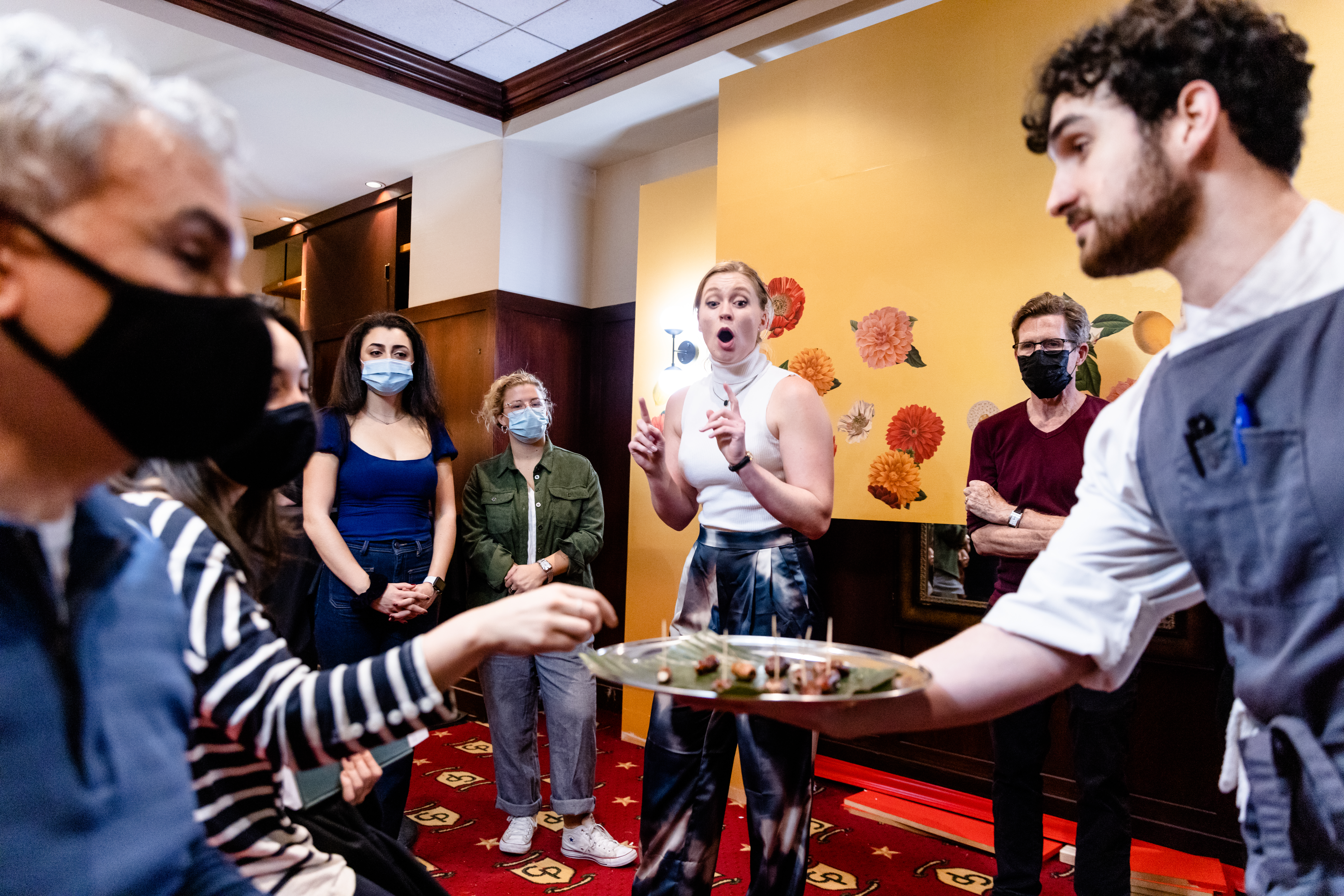 A waiter handing a platter of food to a masked person sitting down while a woman gasps in shock.