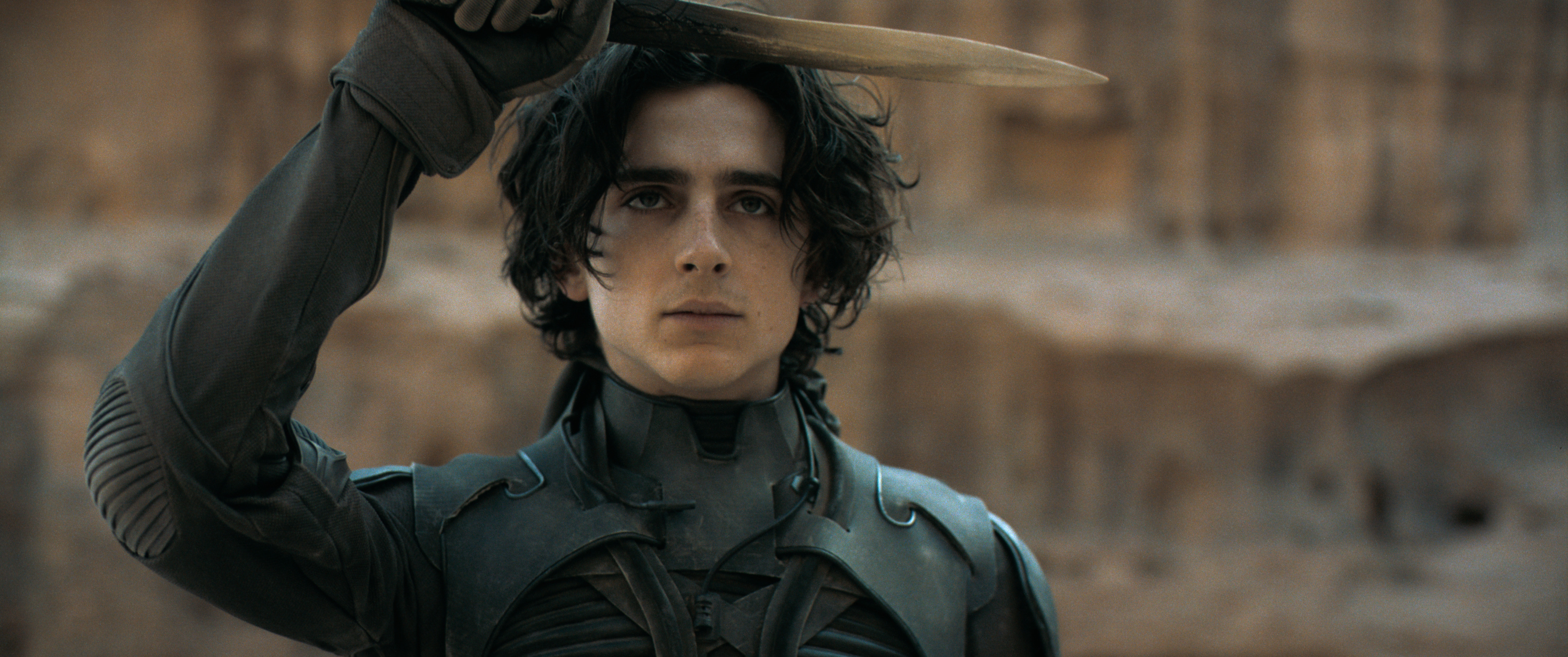 Timothée Chalamet salutes with a crysknife in Dune.