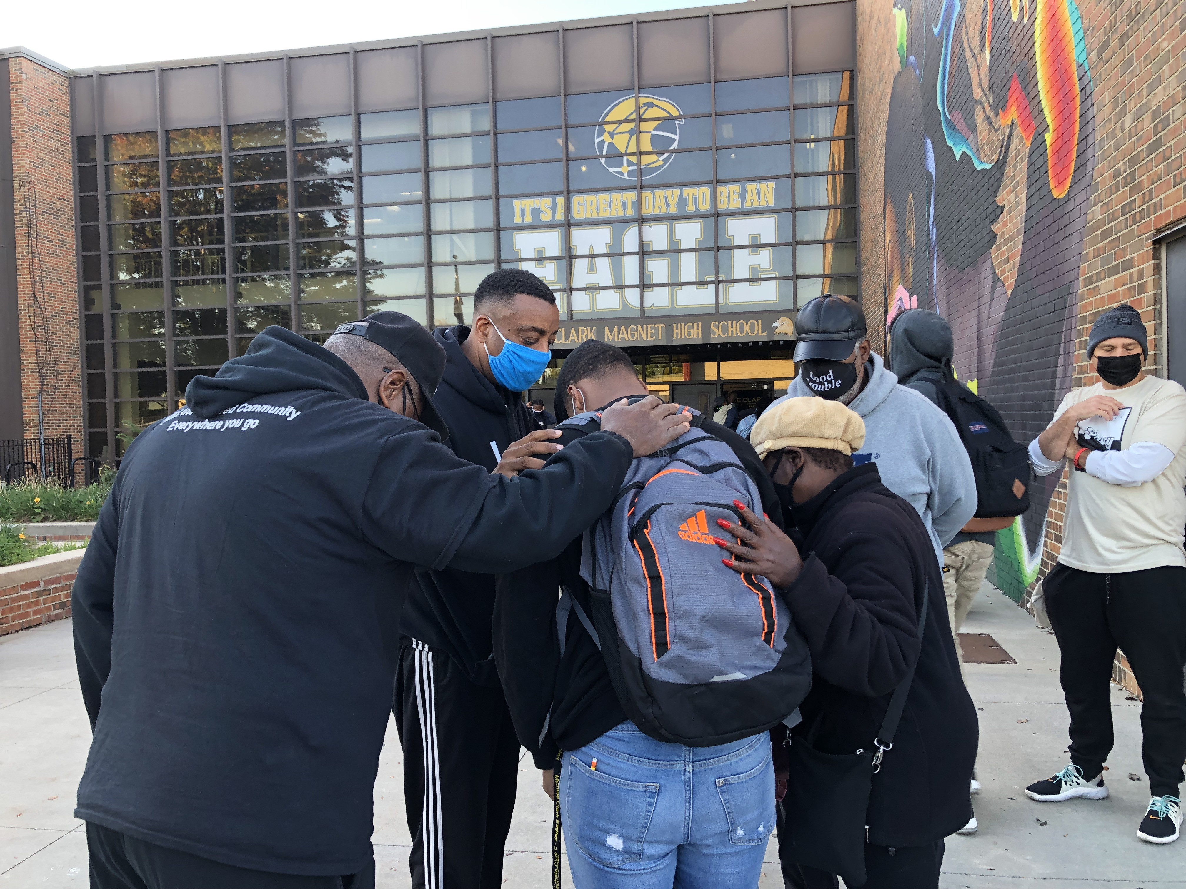 Community activists huddle and pray with a student Monday morning at Michele Clark Academic Prep High School on the West Side.