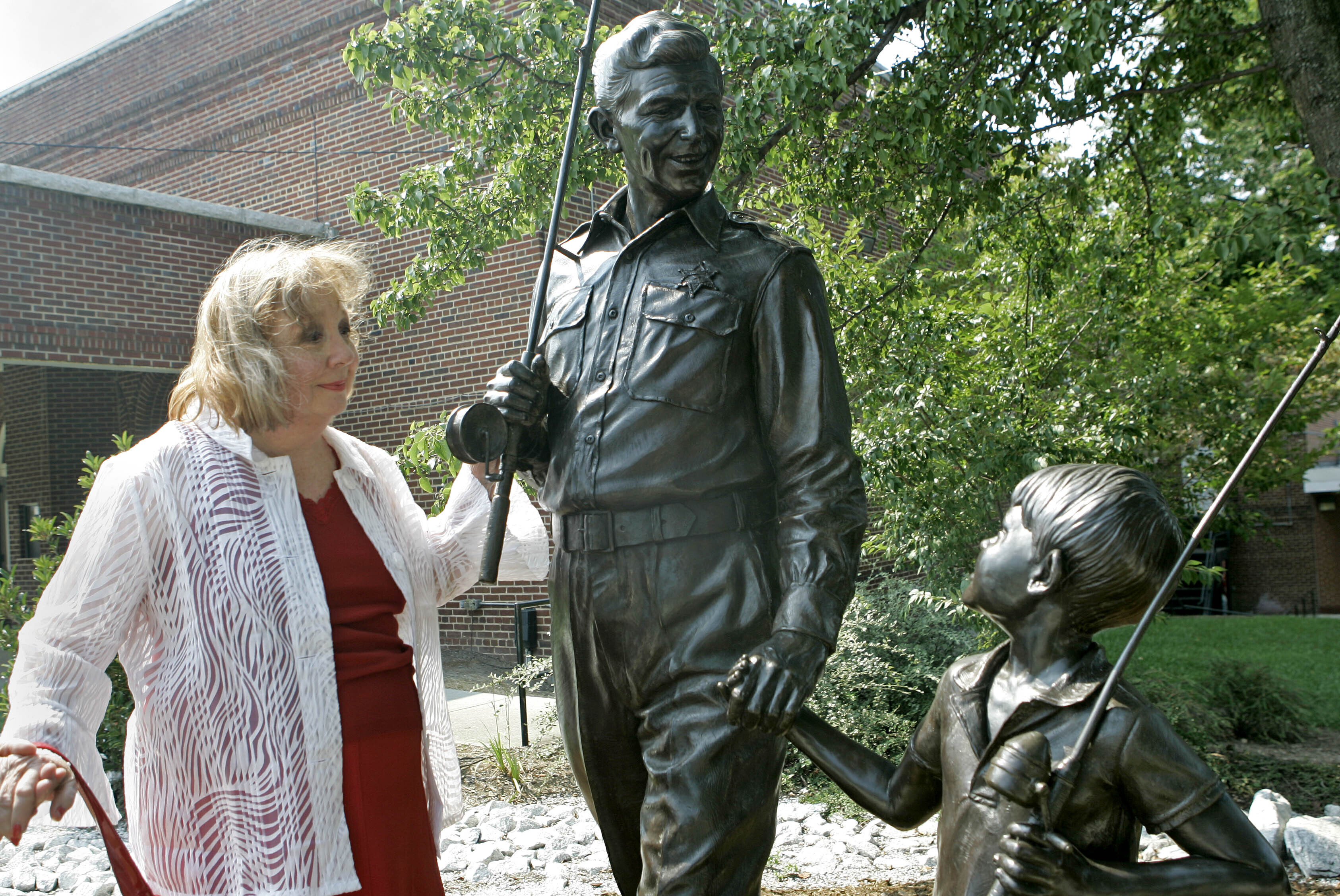 """In this Sept. 6, 2007 file photo, actor Betty Lynn, who played Thelma Lou on """"The Andy Griffith Show,"""" pauses at a statue of Andy and Opie Taylor in Mount Airy, N.C. Lynn died Saturday, Oct. 16, 2021, after a brief illness."""