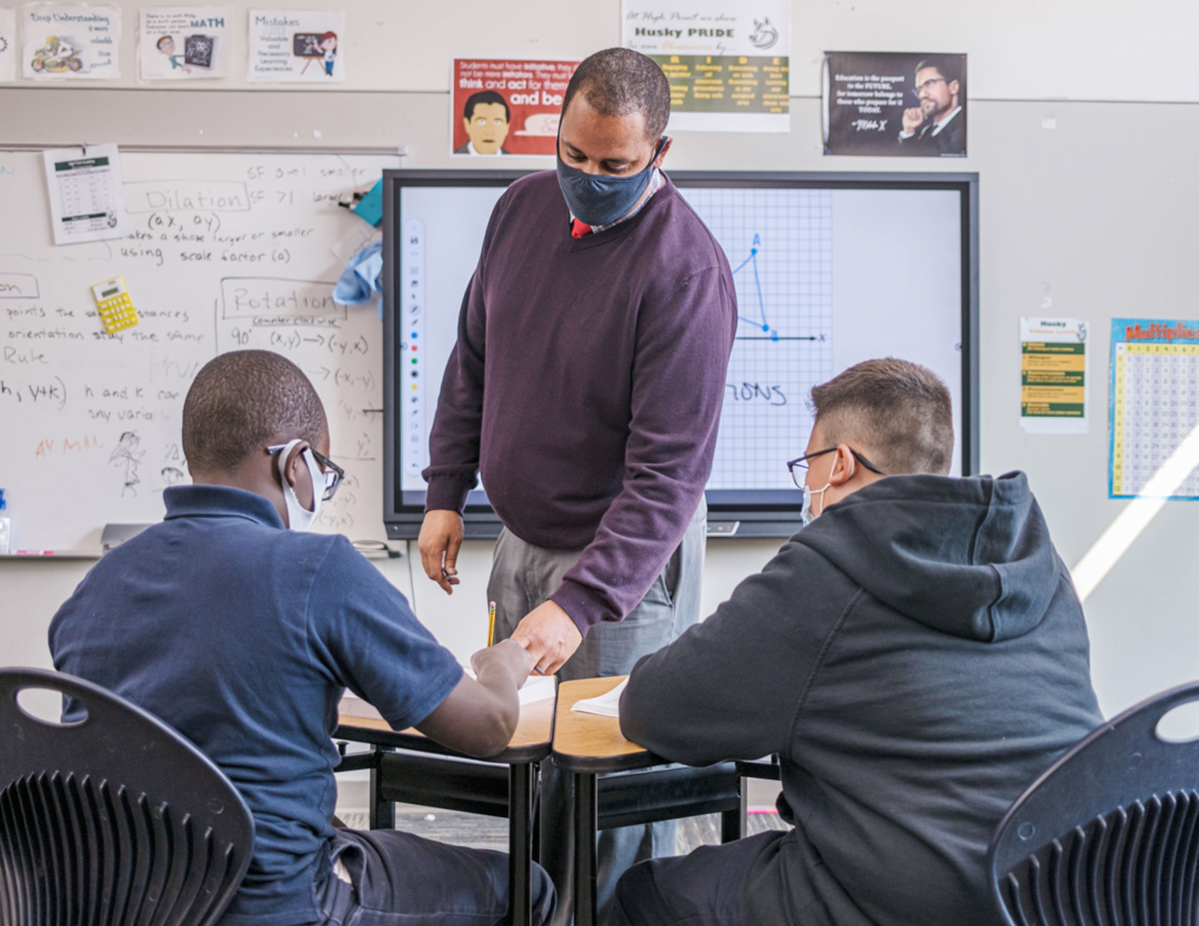 Denver School Board candidate Gene Fashaw, standing in a classroom and wearing a mask, works with two students sitting at their desks in a classroom.