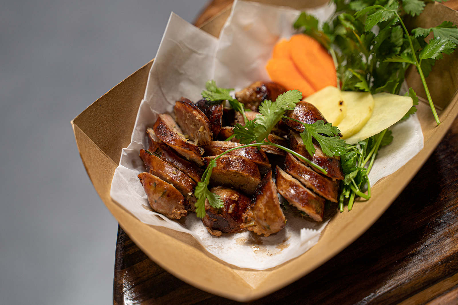Slices of Thai sausage garnished with cilantro, ginger, carrots, and mint.