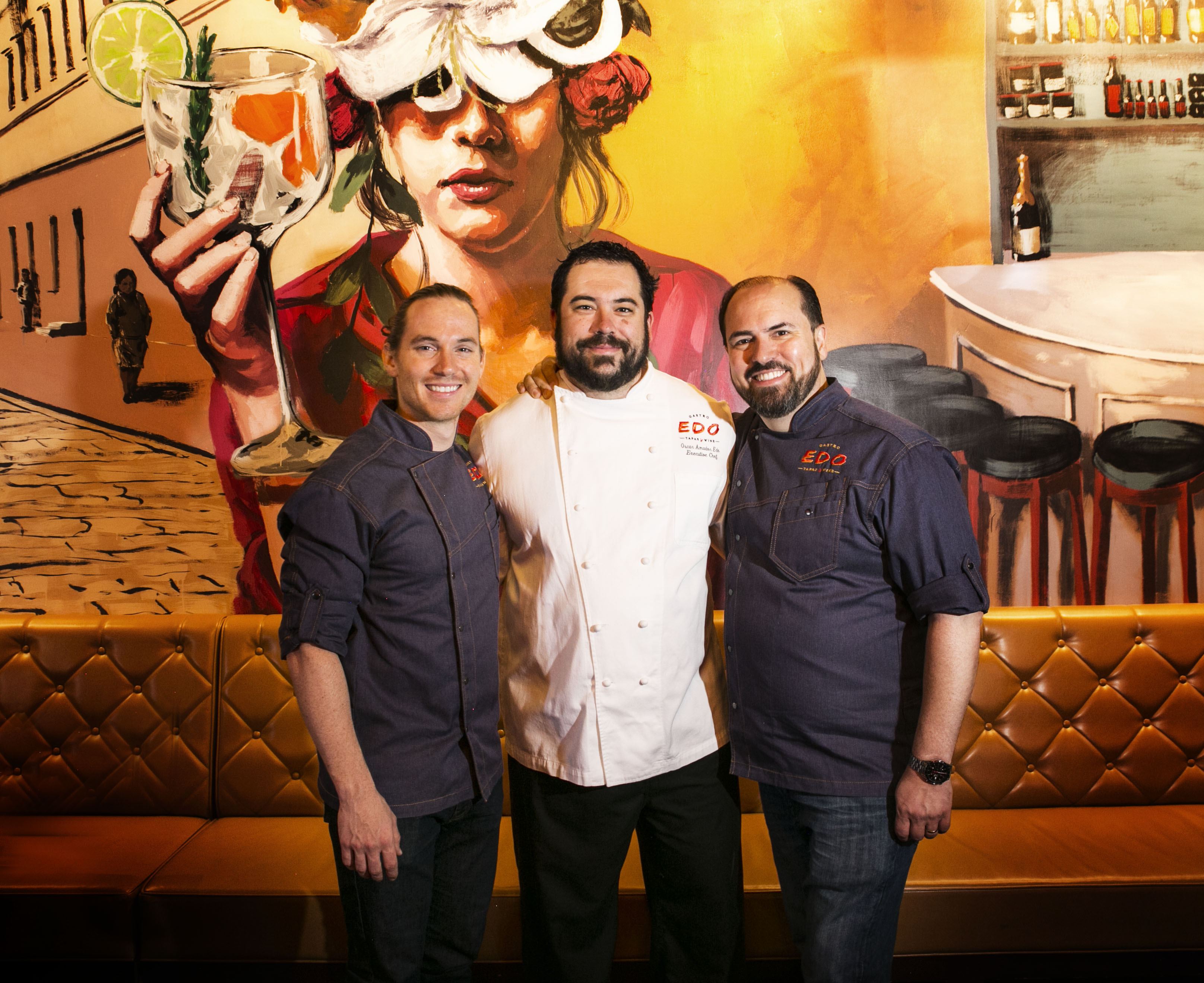 Three men stand in front of a mural at a Spanish restaurant