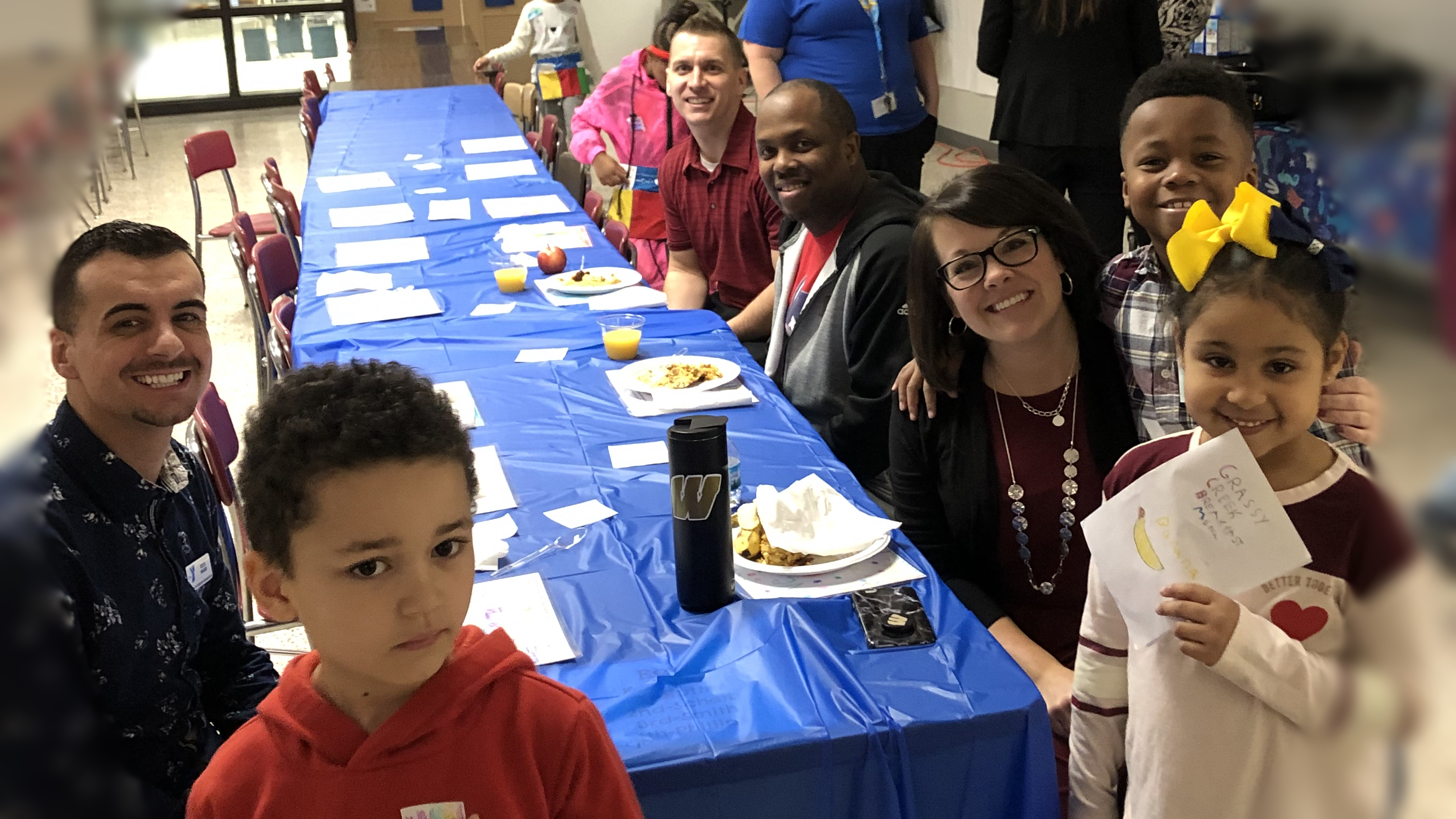 Grassy Creek Elementary School Principal Christy Merchant, students, and staff smile while sitting at a long blue table for breakfast.
