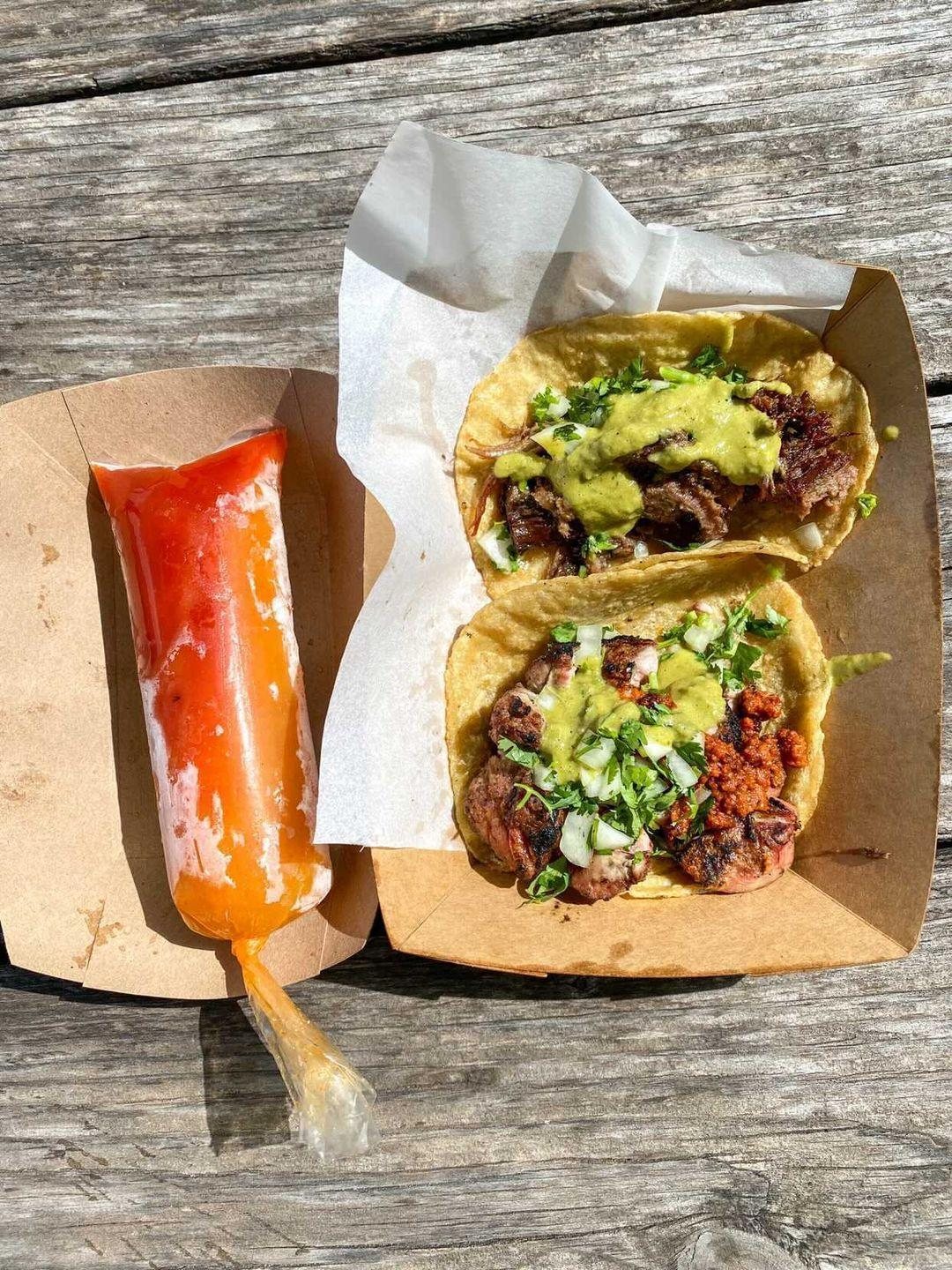 A plastic tube of red-orange and orange frozen liquid next to two corn tortillas filled with meats and green sauce.