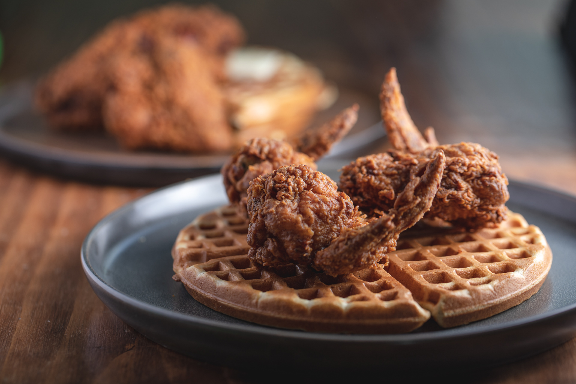 Chicken and waffles from Fixins Soul Kitchen in Downtown LA on a dark plate.