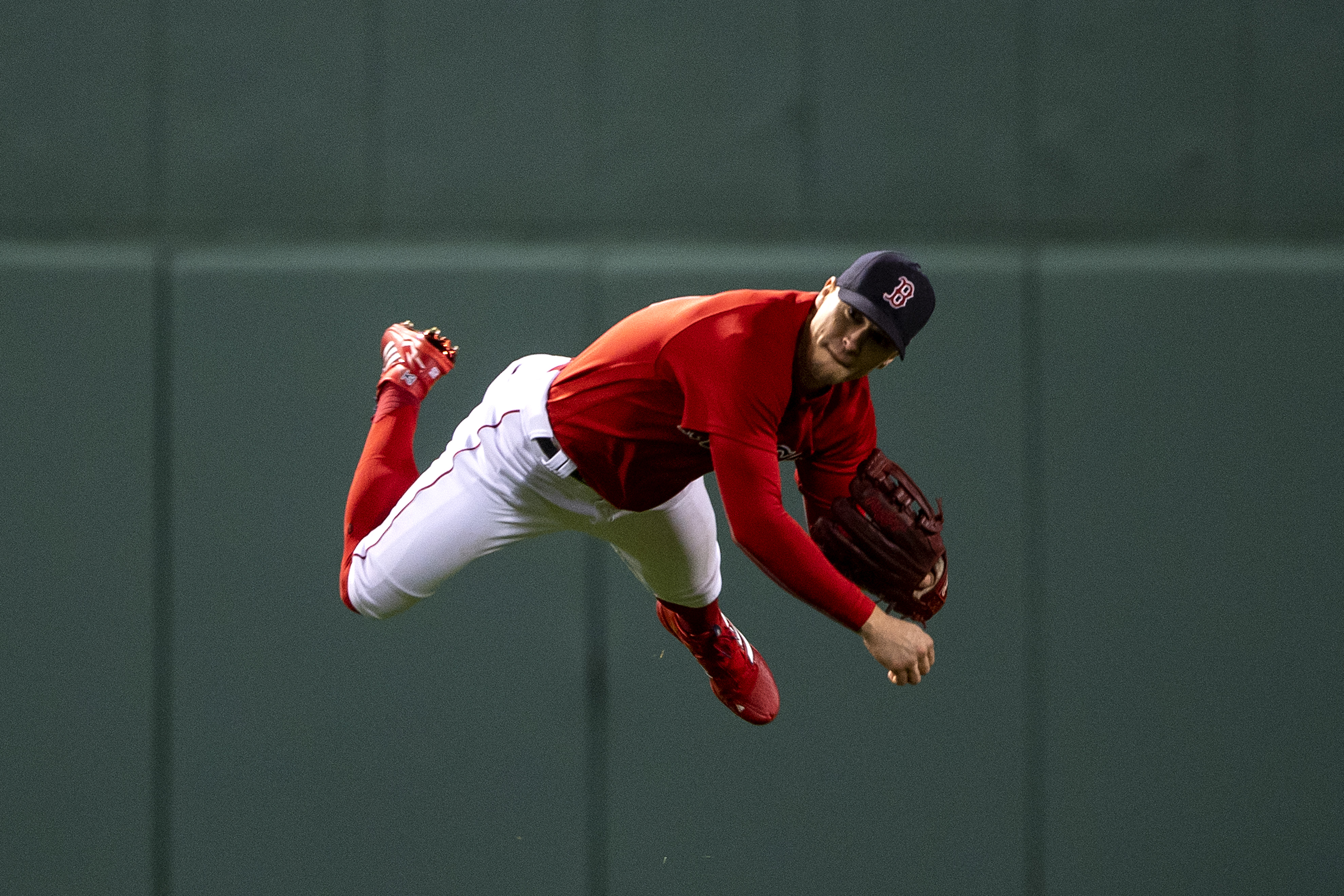 Enrique Hernandez #5 of the Boston Red Sox falls as he throws during the fourth inning of game three of the 2021 American League Championship Series against the Houston Astros at Fenway Park on October 18, 2021 in Boston, Massachusetts.
