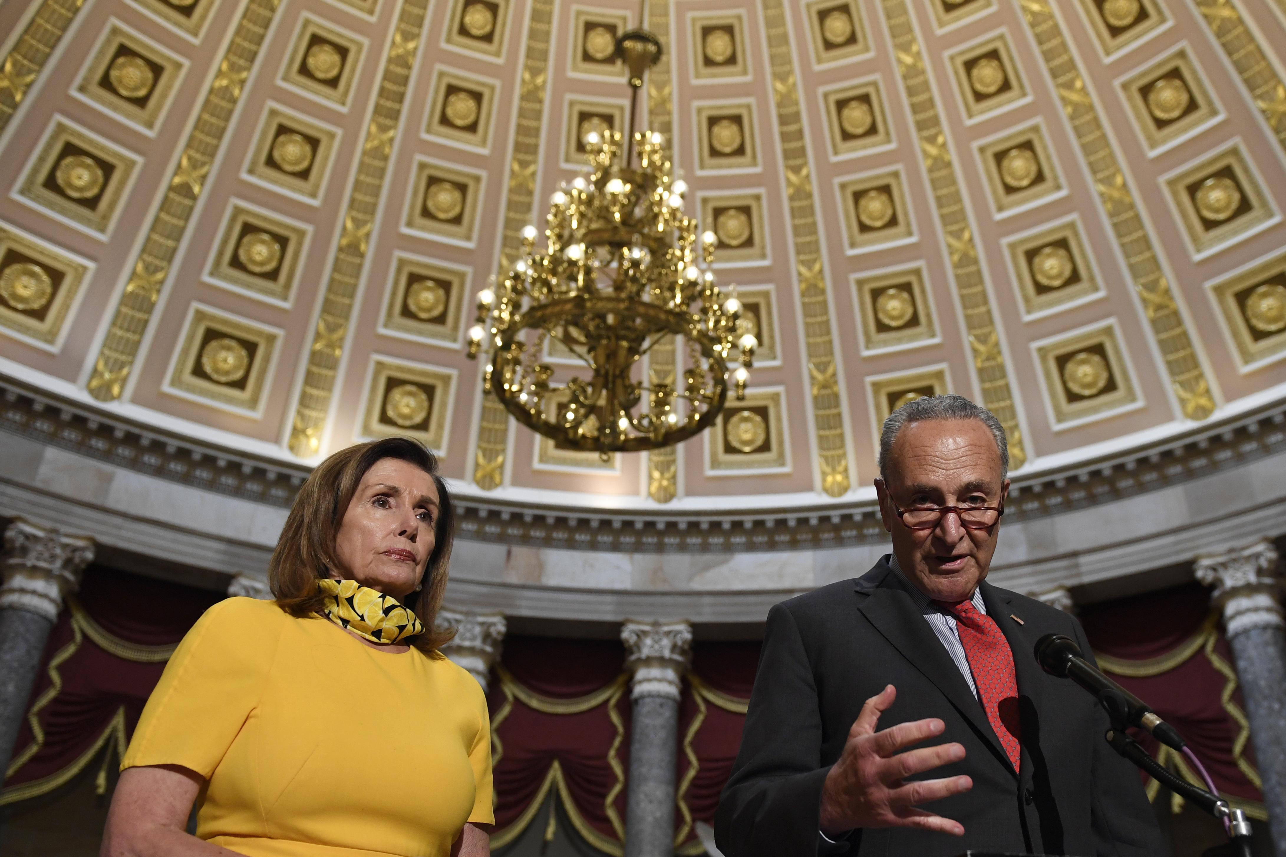 House Speaker Nancy Pelosi, of Calif., left, listens to Senate Minority Leader Sen. Chuck Schumer, of N.Y., on Capitol Hill.
