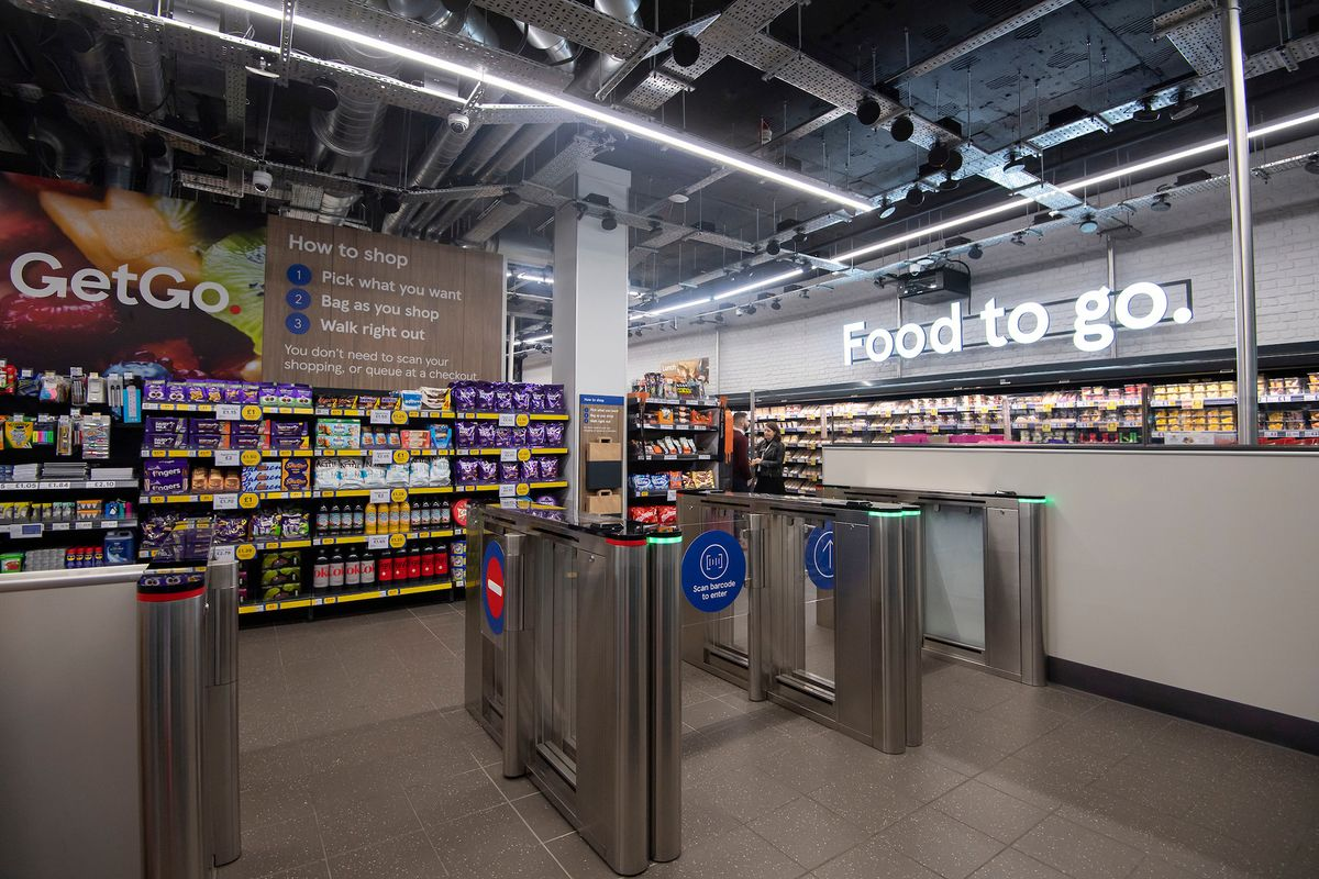 A photo of the entrance and exit to Tesco's no-checkout supermarket in London, with plastic barriers
