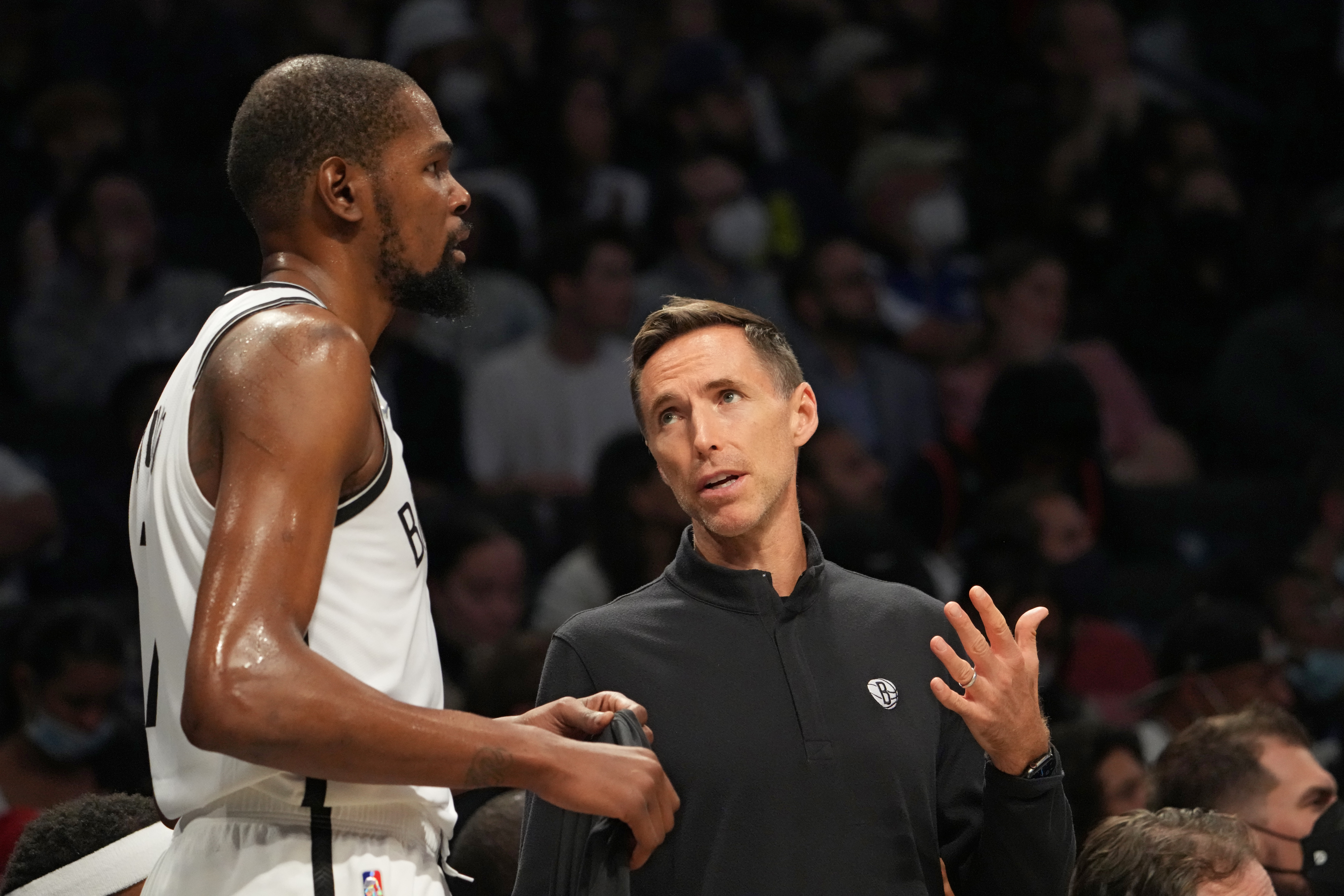 Kevin Durant #7 of the Brooklyn Nets and Head Coach Steve Nash of the Brooklyn Nets talk during a preseason game on October 14, 2021 at Barclays Center in Brooklyn, New York.