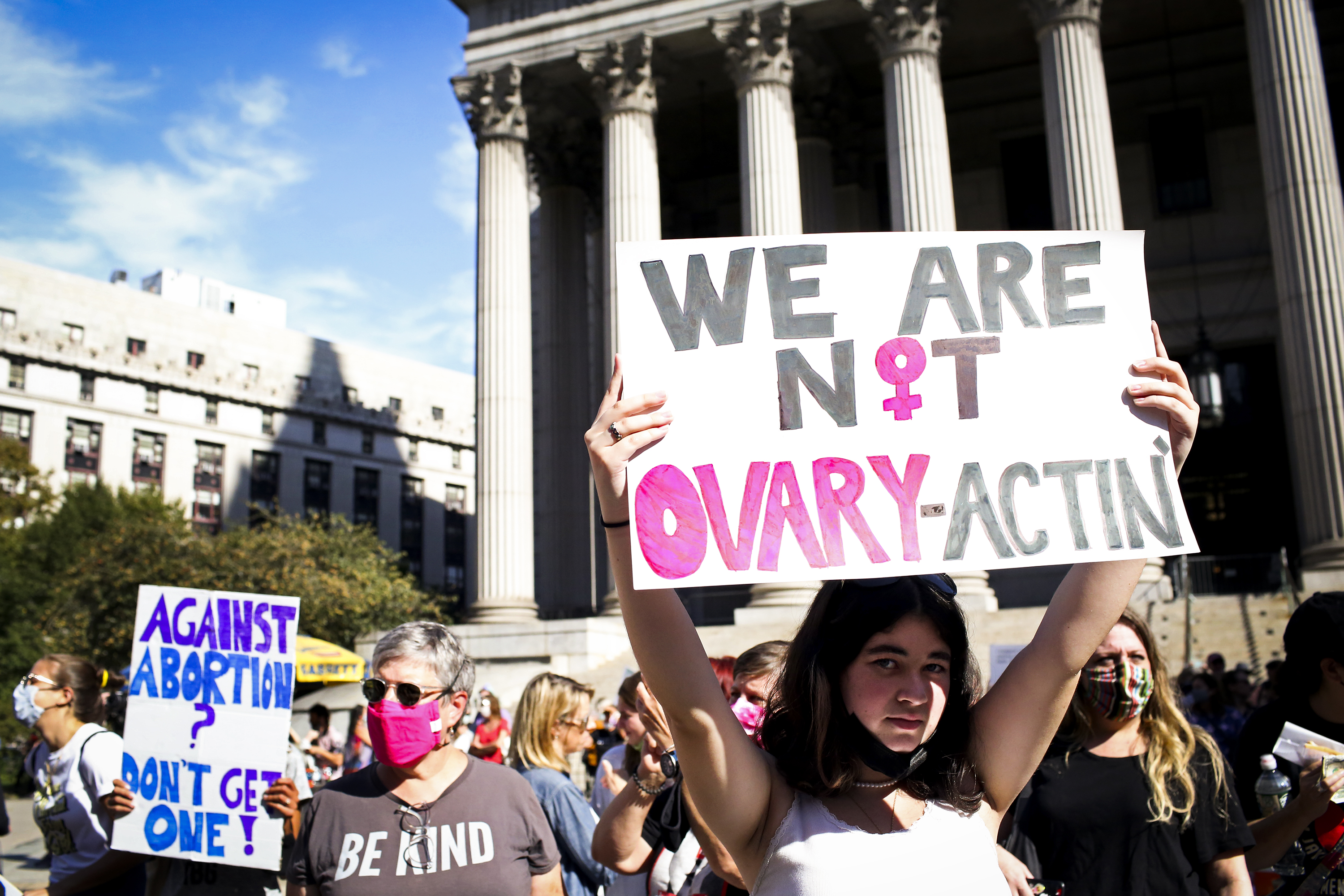 """A protesters holds up a sign that reads """"We are not ovary-actin."""""""