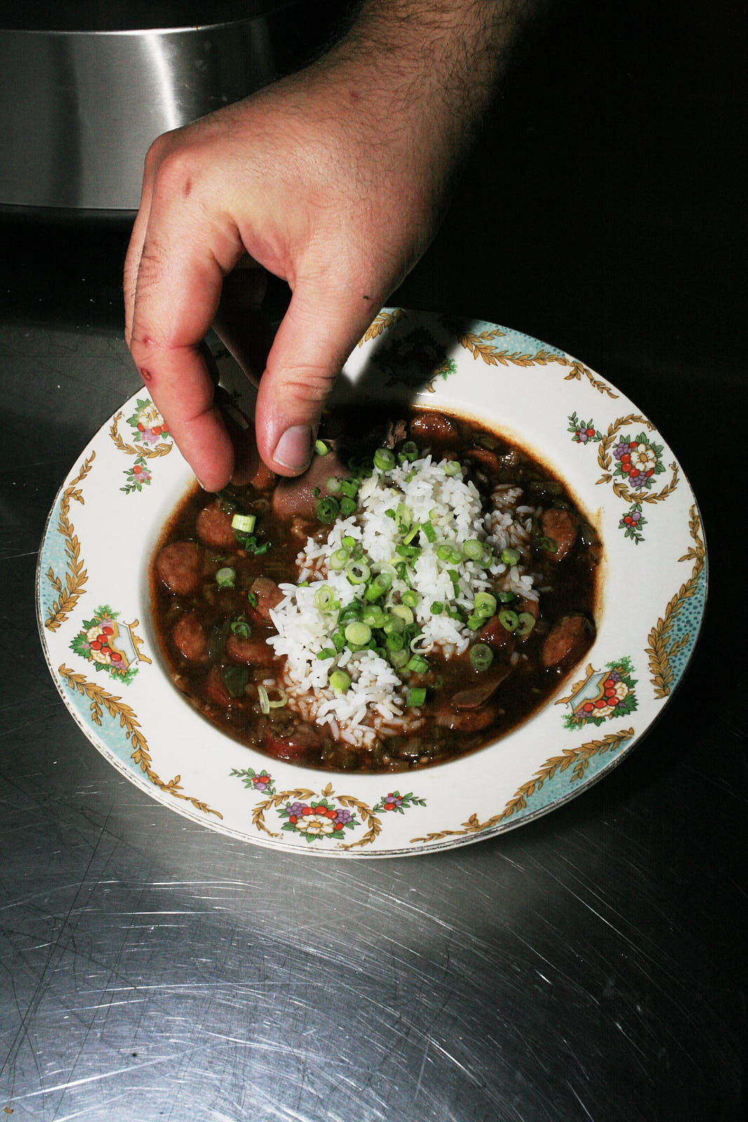 A shallow, floral-patterned china bowl of the gumbo, now with white rice and spring onions added.