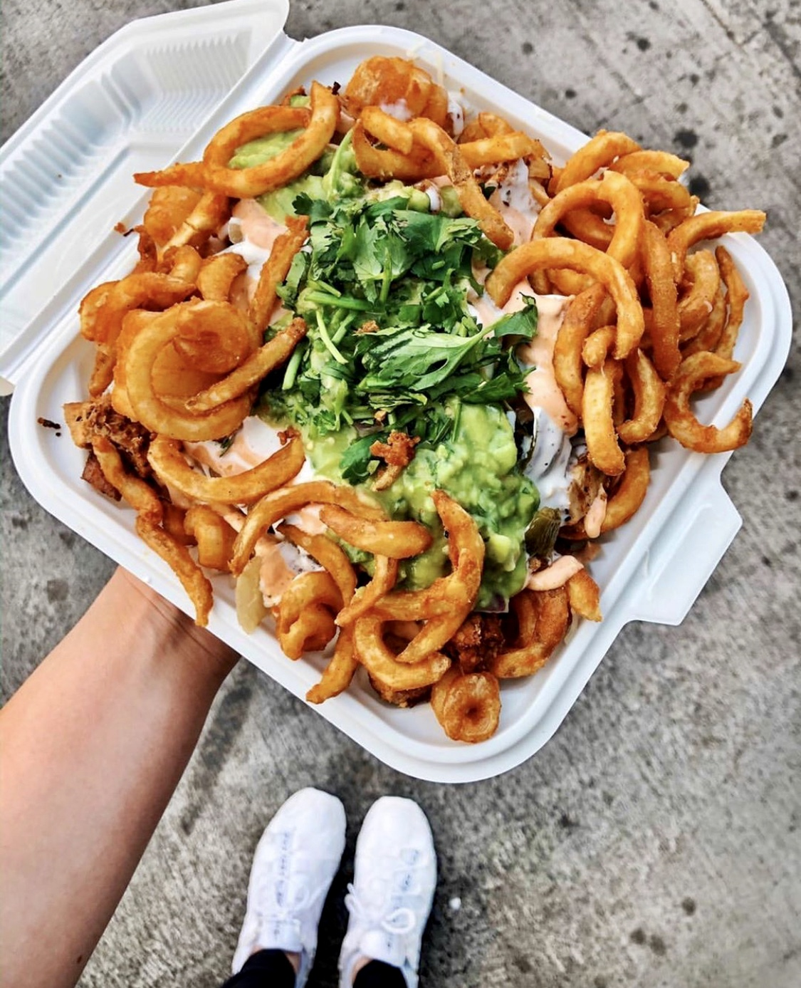 curly fries topped with guacamole in styrofoam container