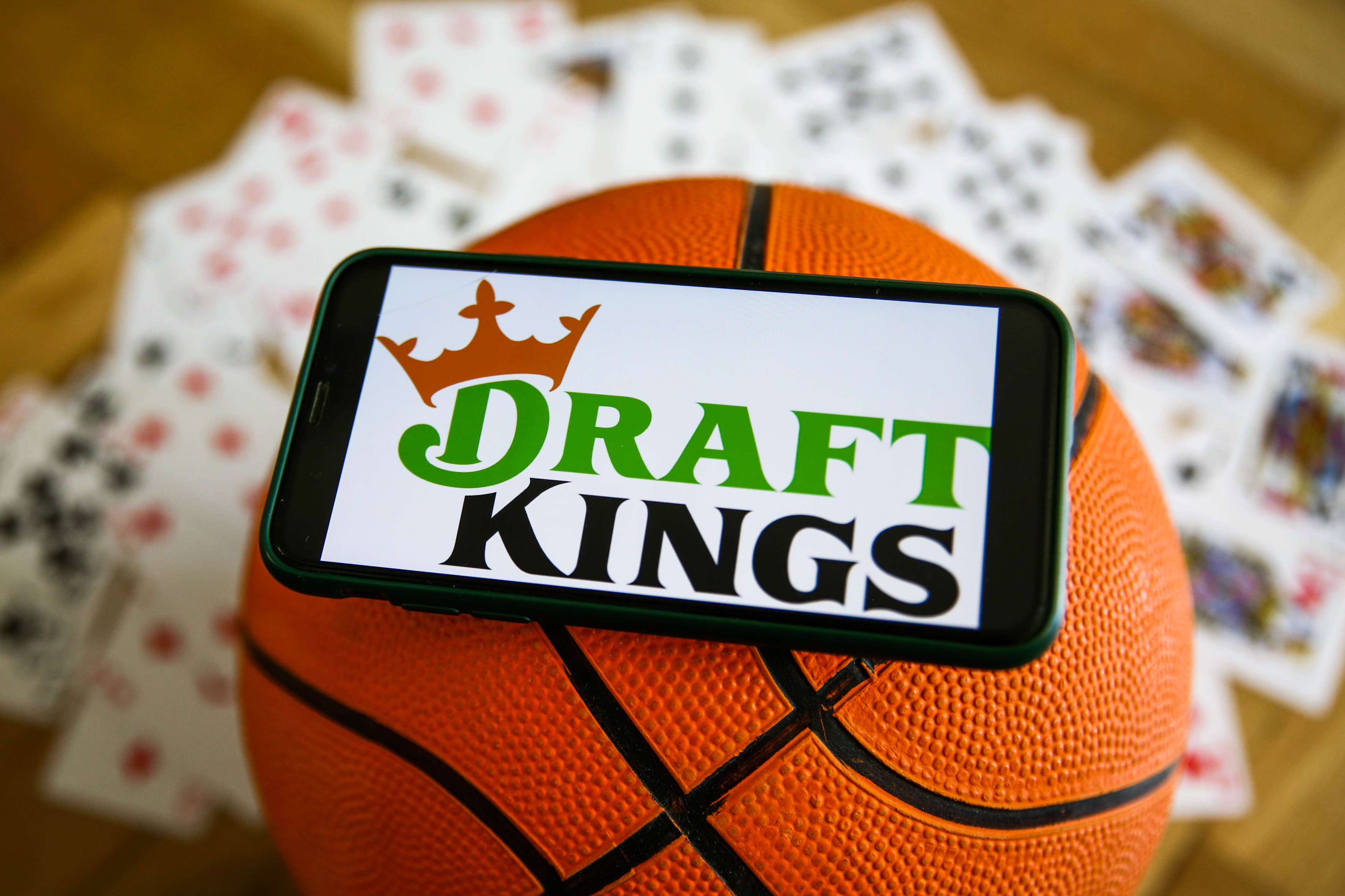 DraftKings logo displayed on a mobile phone, a basketball and playing cards are seen in this illustration photo taken in Krakow, Poland on September 21, 2021.