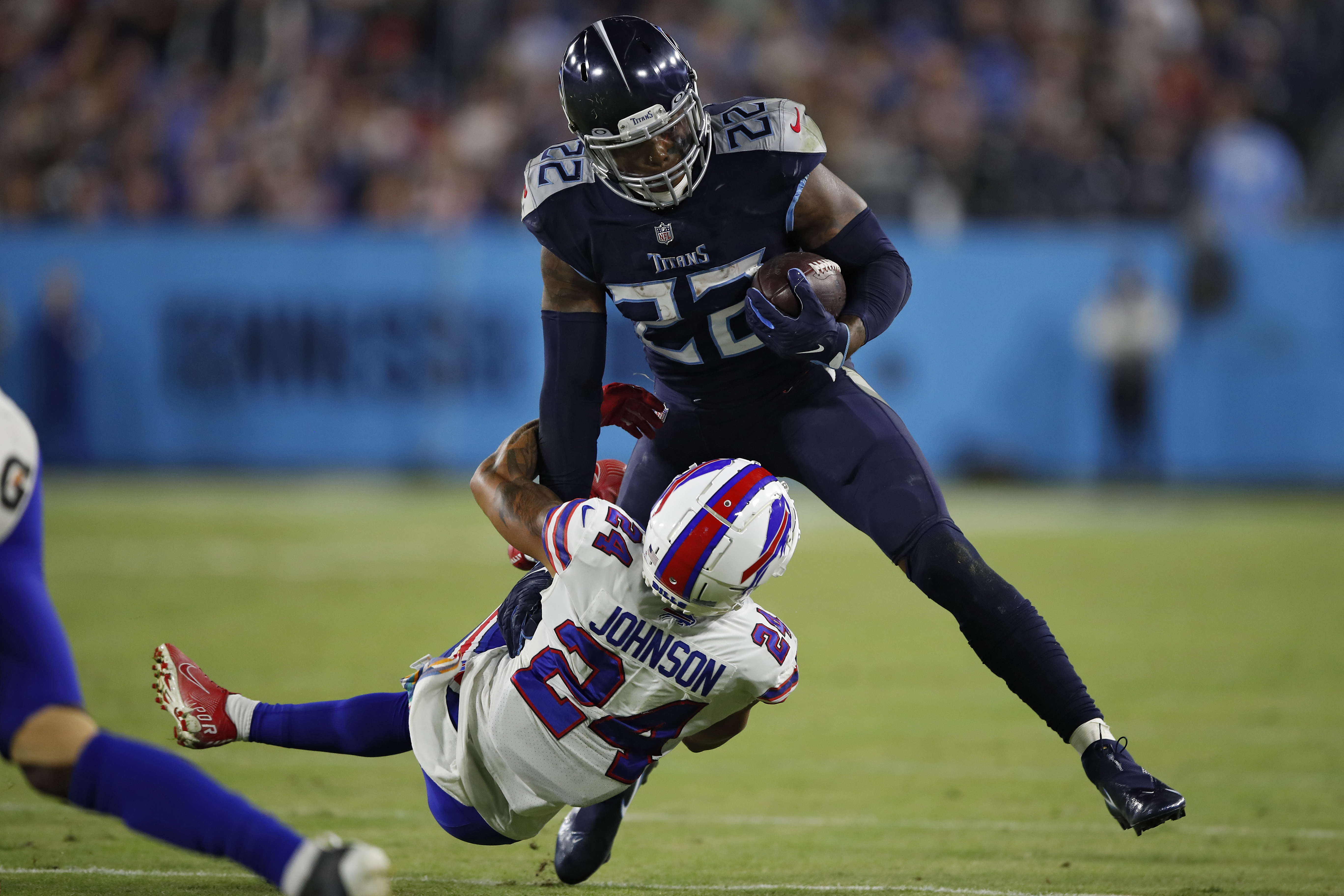 Running back Derrick Henry #22 of the Tennessee Titans rushes in front of cornerback Taron Johnson #24 of the Buffalo Bills during the second half at Nissan Stadium on October 18, 2021 in Nashville, Tennessee.