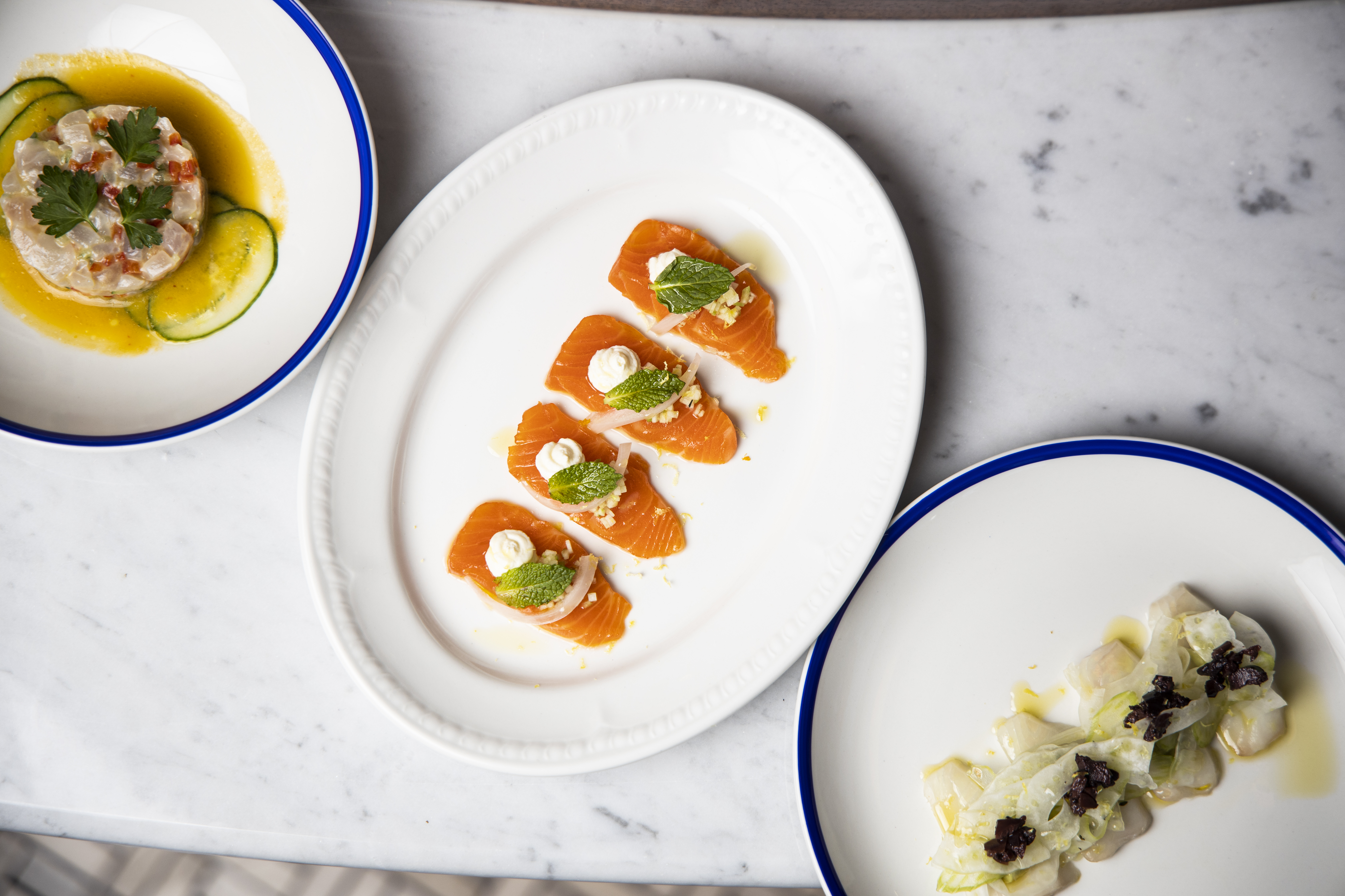 Three plates of crudo at Salt Line placed on a marble table.