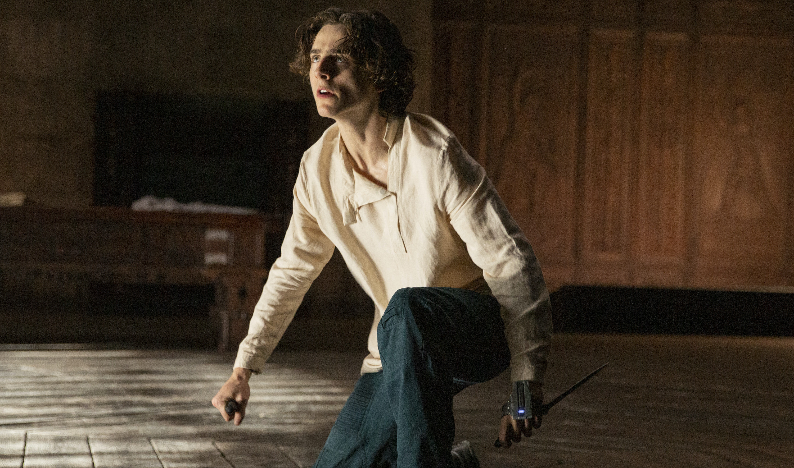 Timothée Chalamet as as Paul Atreides crouches on the floor and clutches a knife in Dune