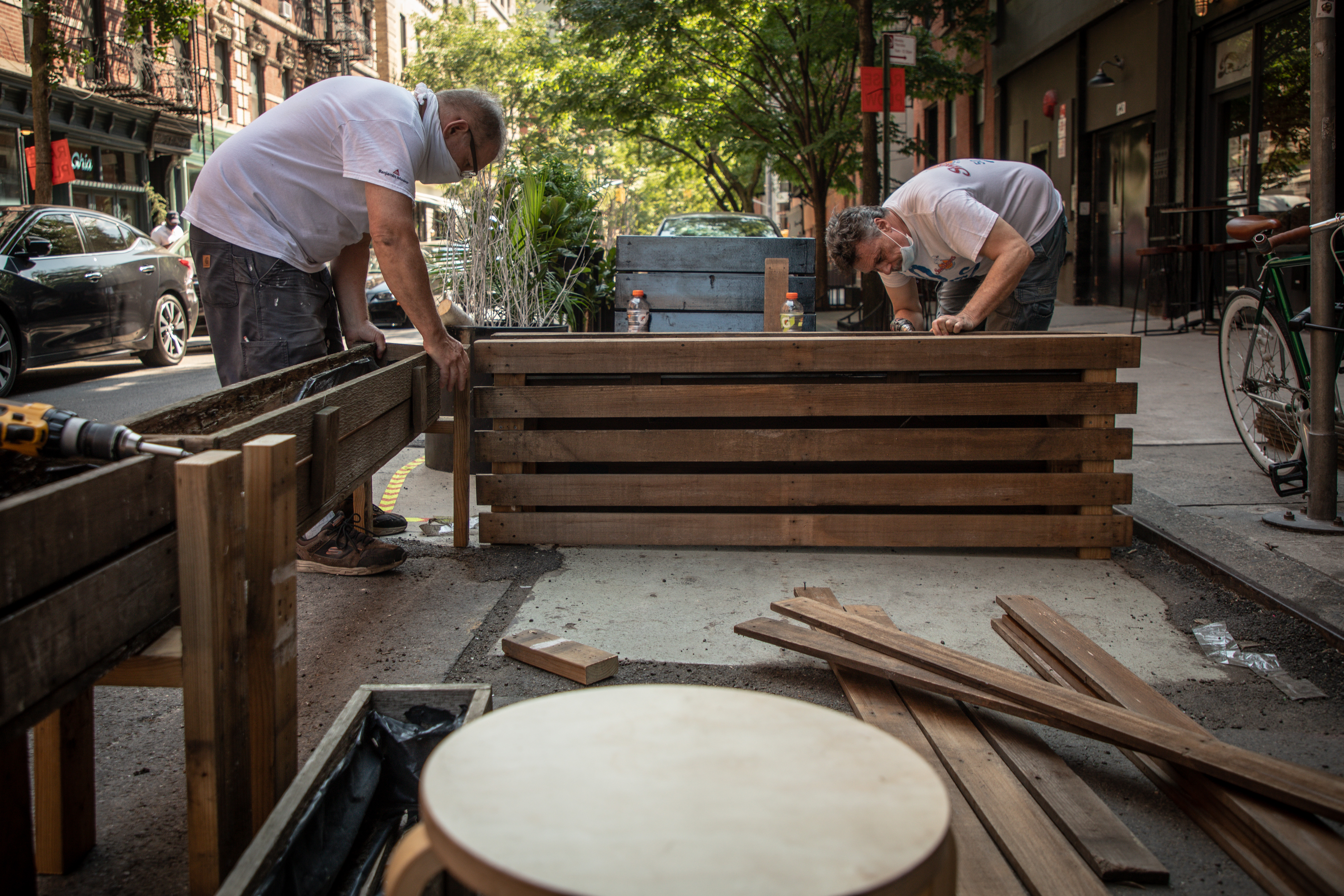 Two workers can be seen installing barriers on the street outside a restaurant