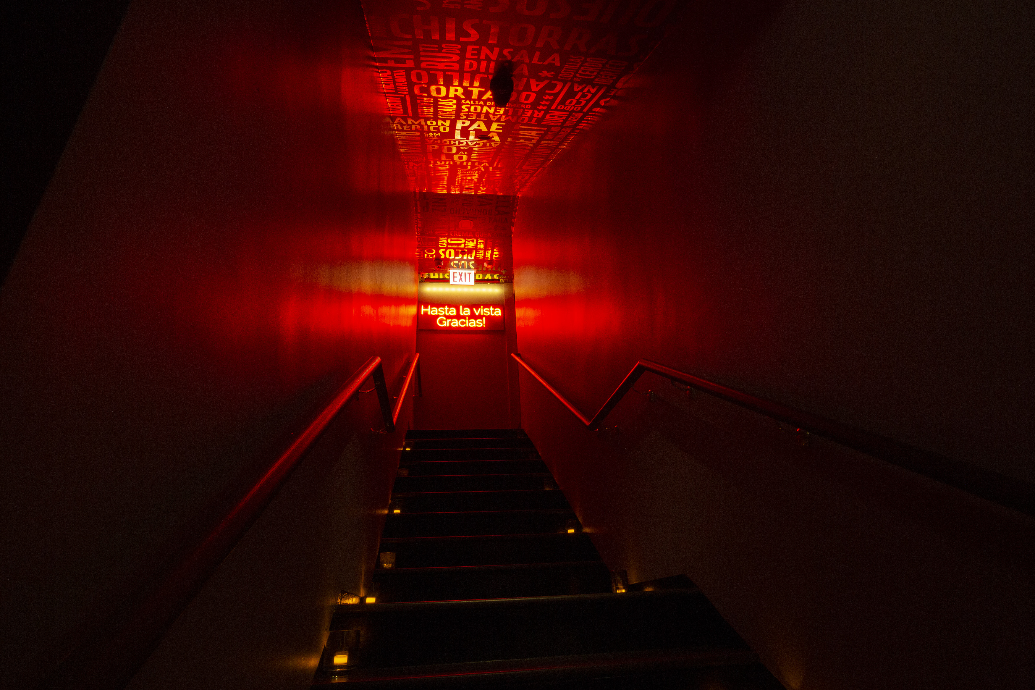 """A dark stairwell leads up to a glowing, red-lit door with a red neon sign that reads """"Hasta la vista. Gracias!"""""""
