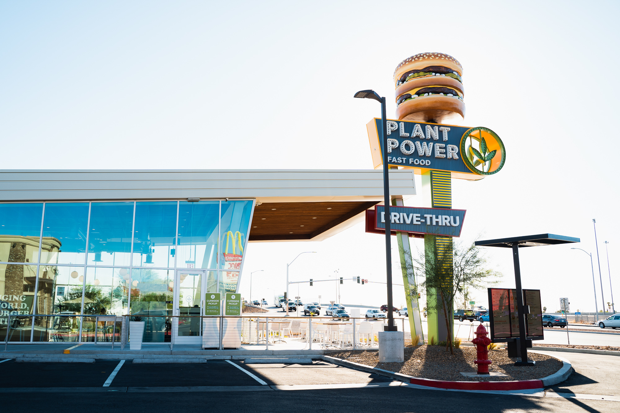 outside of burger joint with wall to ceiling windows and large burger sign