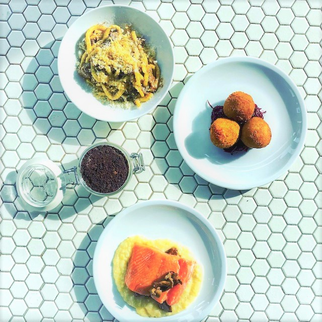 Three dishes and a mason jar filled with tiramisu are arranged over a white tile background.