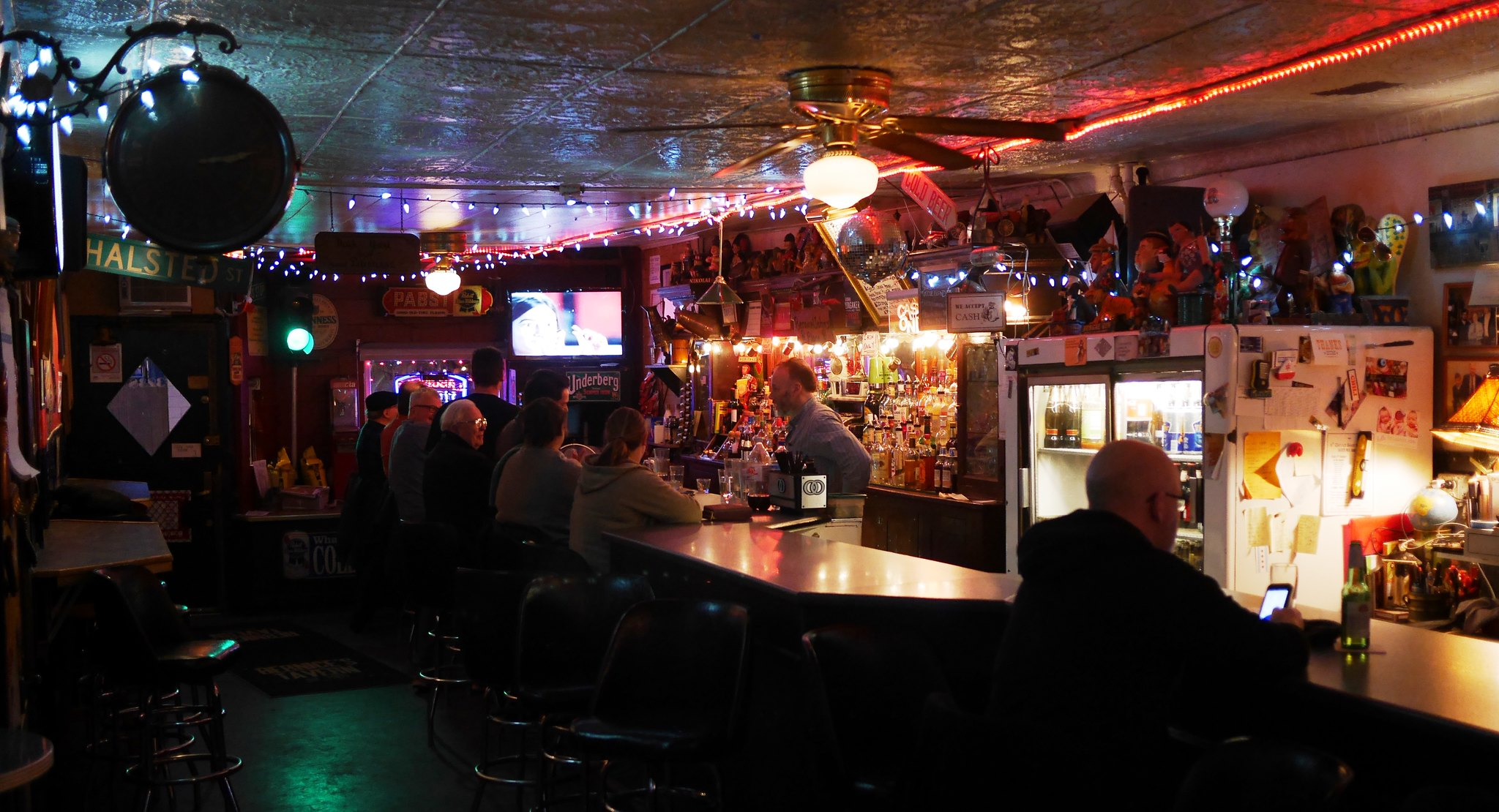 A dimly lit dive bar with folks sitting on stools at a wooden bar, with light illuminating the liquor bottles.