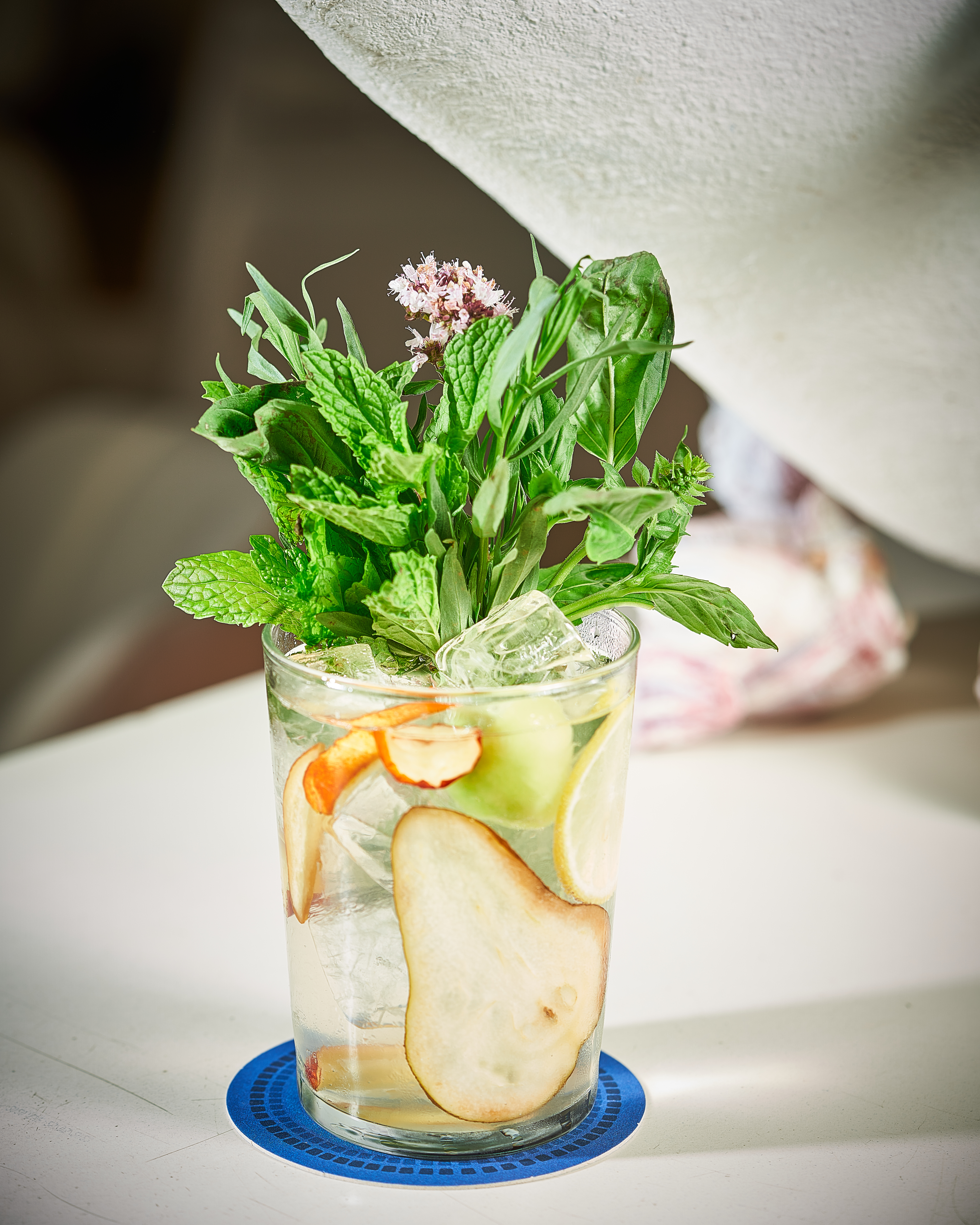 A clear cocktail in short glass filled with fruit and a bouquet of herbs including mint and basil.