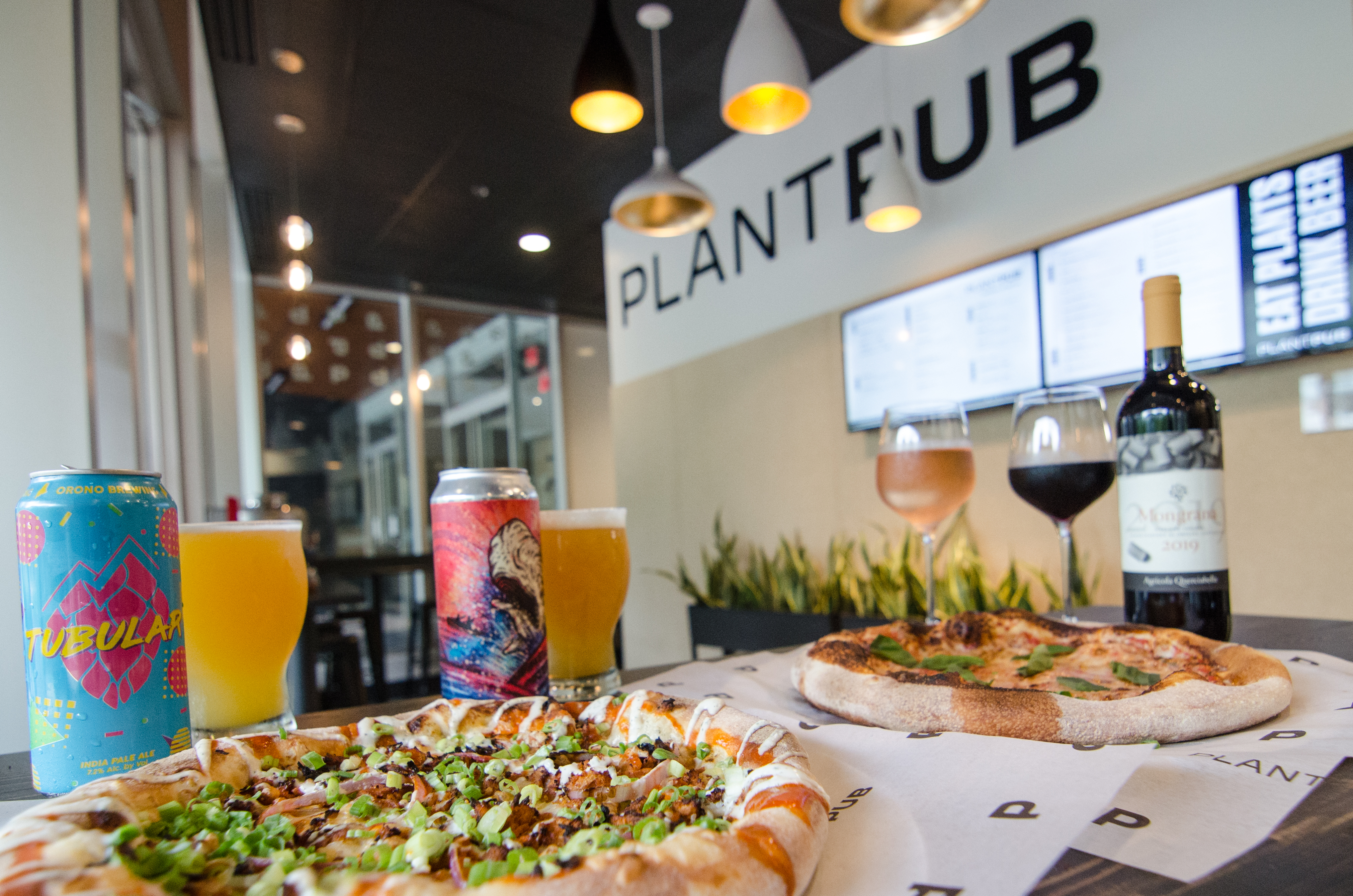 A table of pizza, beer, and wine is visible inside a casual restaurant, with PlantPub written on the wall.