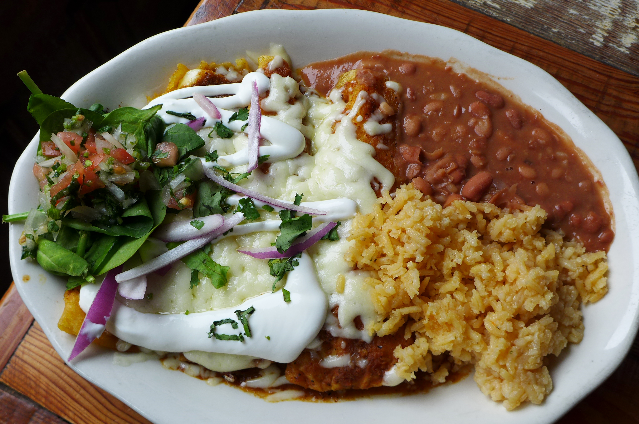 Enchiladas smothered in cheese and sided with beans and rice.