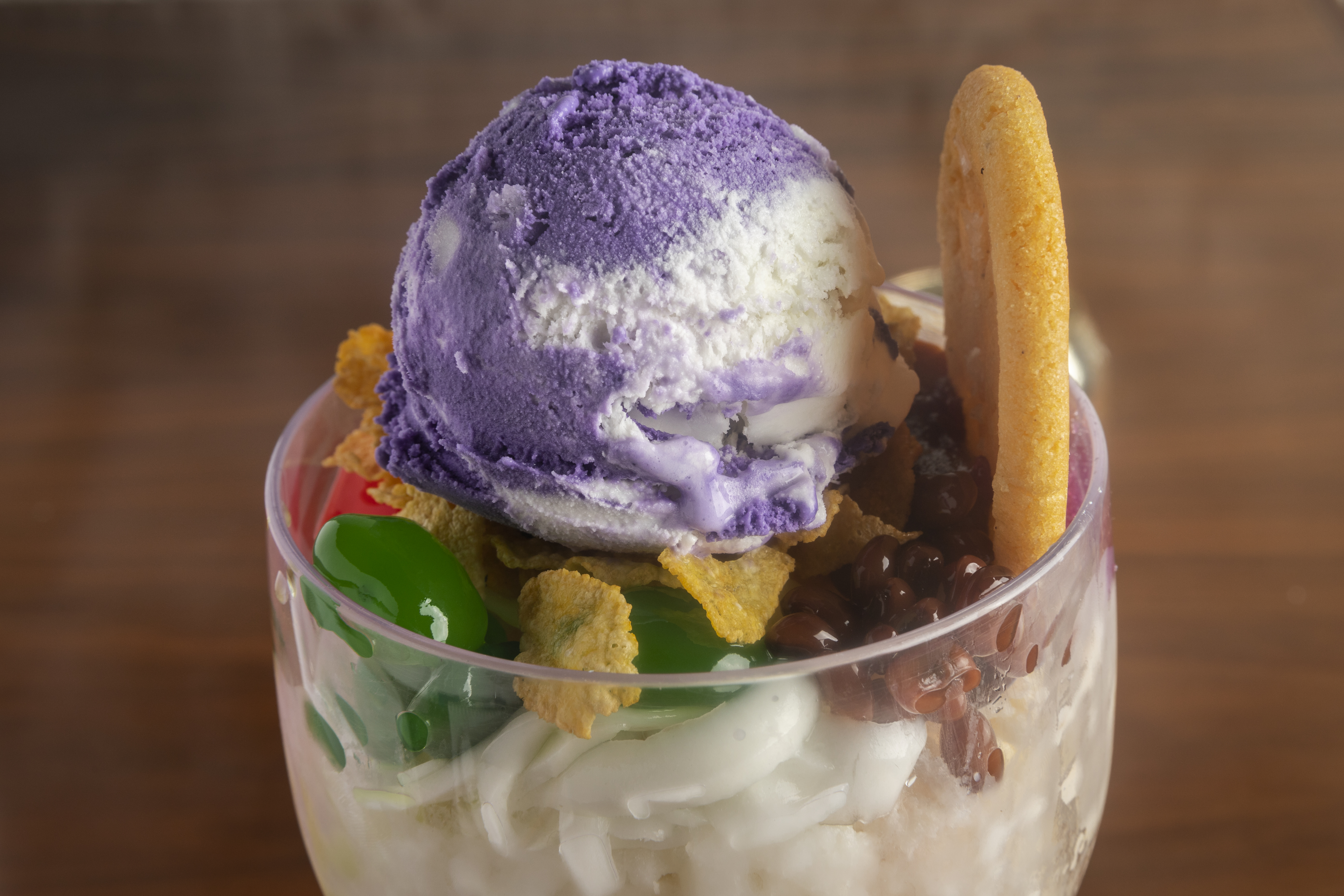 A close-up view of Filipino dessert halo halo, a scoop of purple and white ice cream on top of a pile of multi-colored jellies.