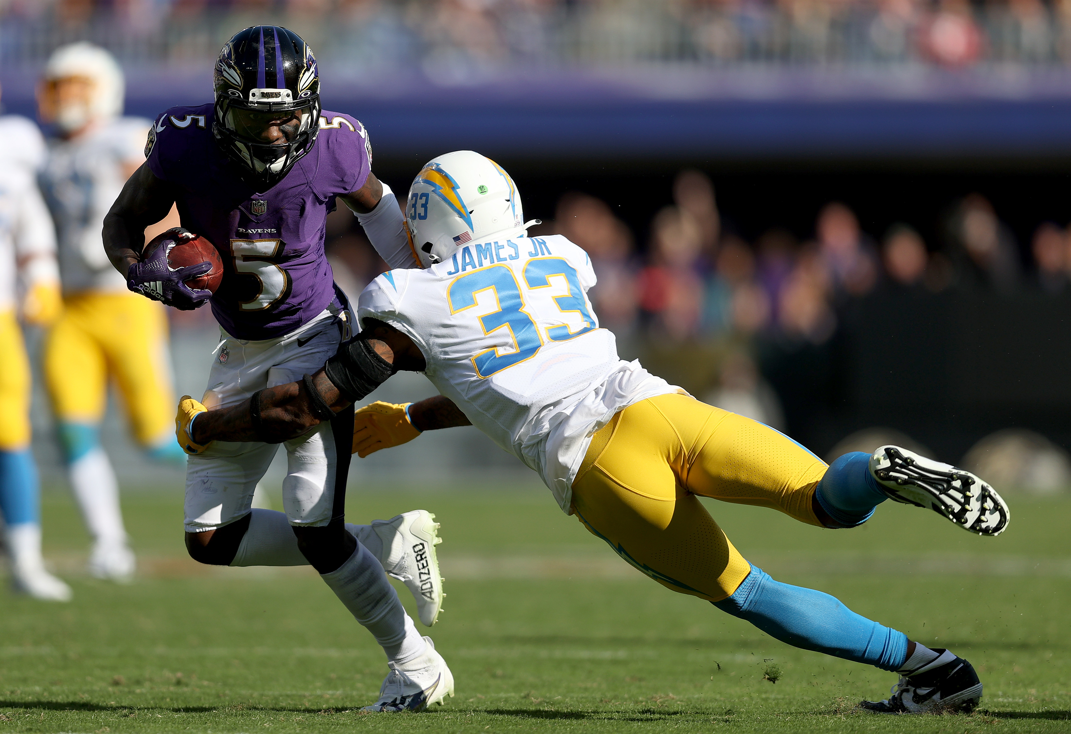 Derwin James Jr. #33 of the Los Angeles Chargers tackles Marquise Brown #5 of the Baltimore Ravens during the third quarter at M&T Bank Stadium on October 17, 2021 in Baltimore, Maryland.