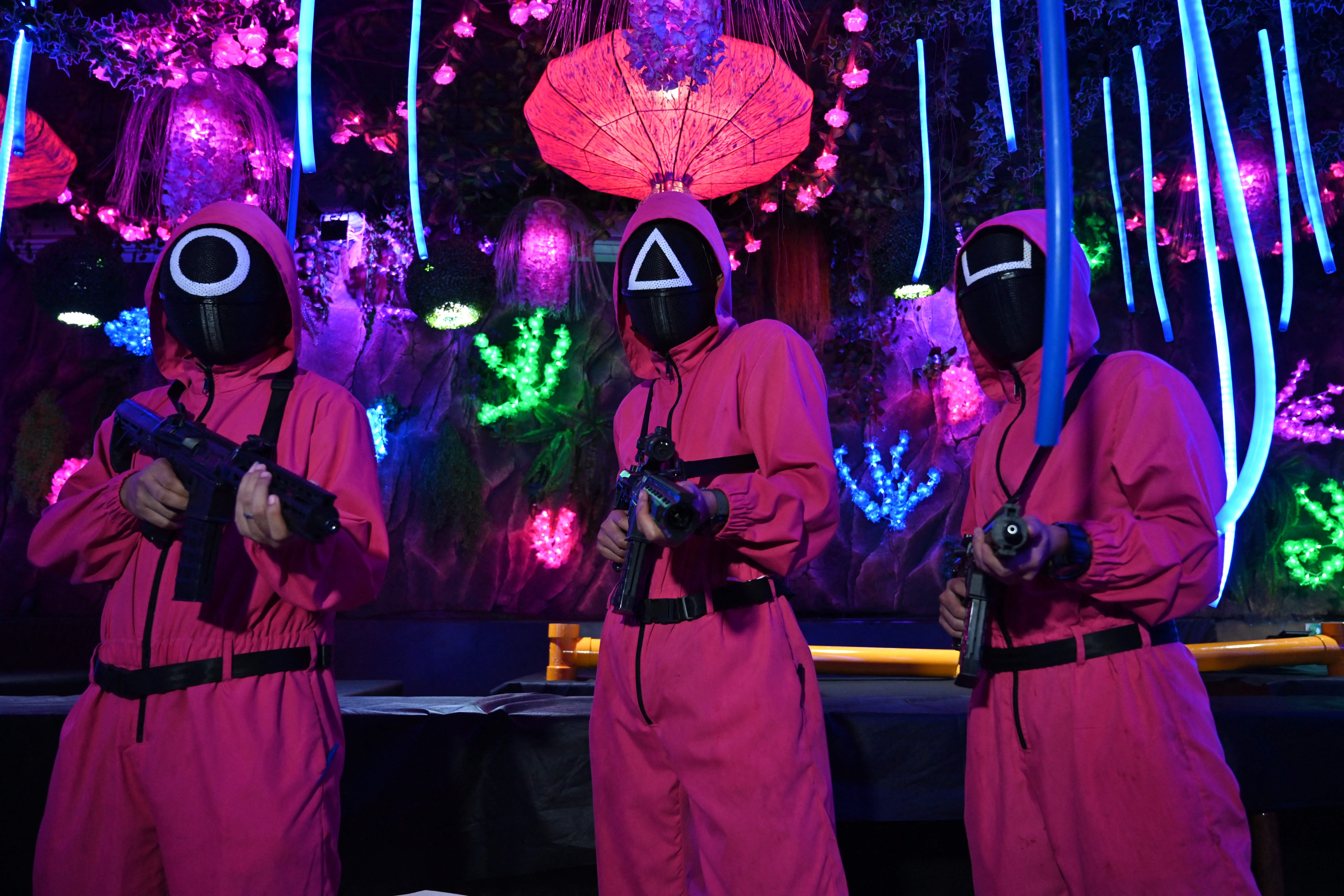 Waiters at a cafe in Jakarta pose for the camera while dressed as soldiers from the Netflix series Squid Game on October 19, 2021