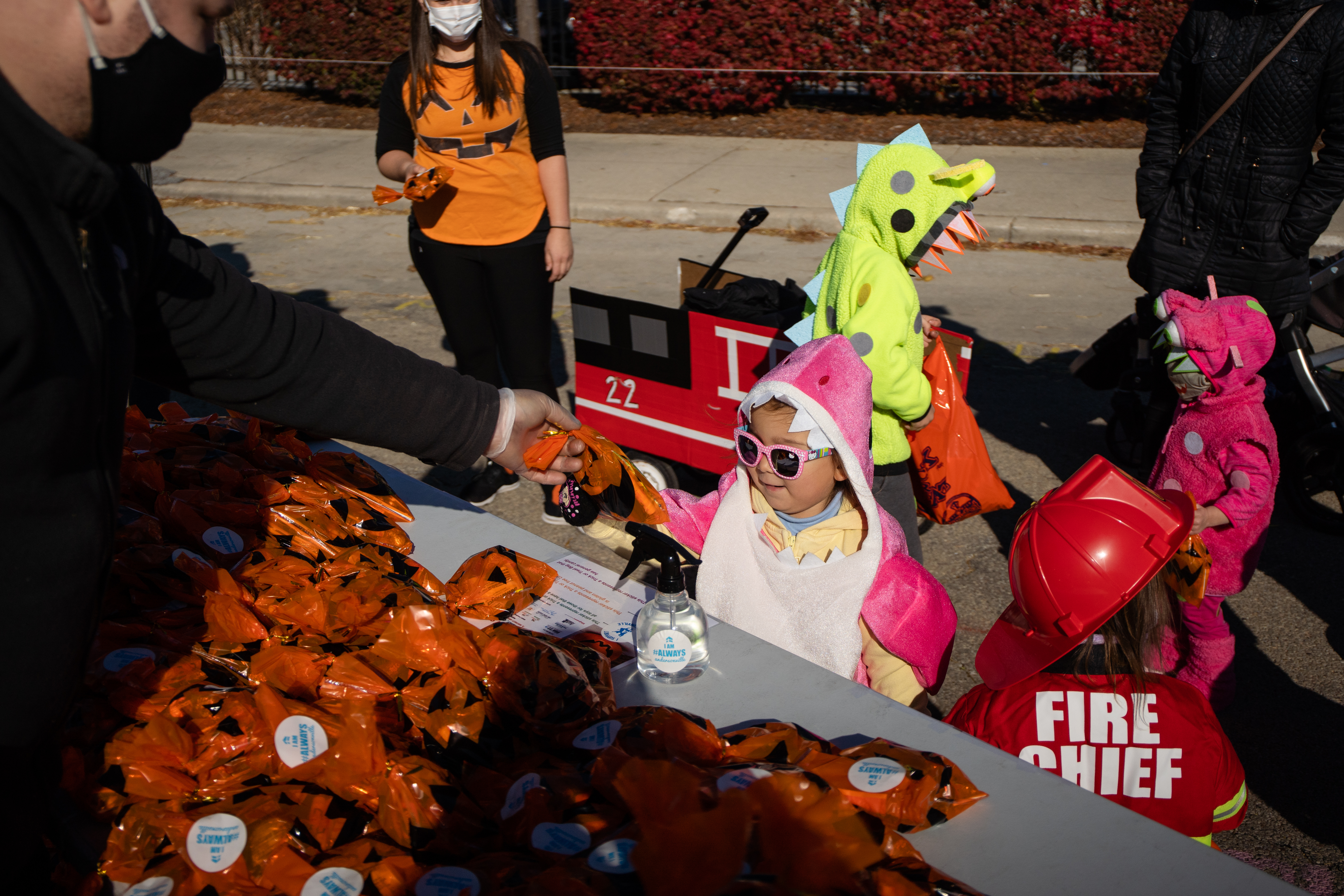 """Adrianna Jose, 3, receives candy during the Andersonville Chamber of Commerce's """"Halloween on Catalpa"""" trick-or-treating event near West Catalpa Avenue and North Clark Street in Andersonville, on Halloween 2020. People are still encouraged to wear masks and come up with socially distant ways to celebrate this year, too."""